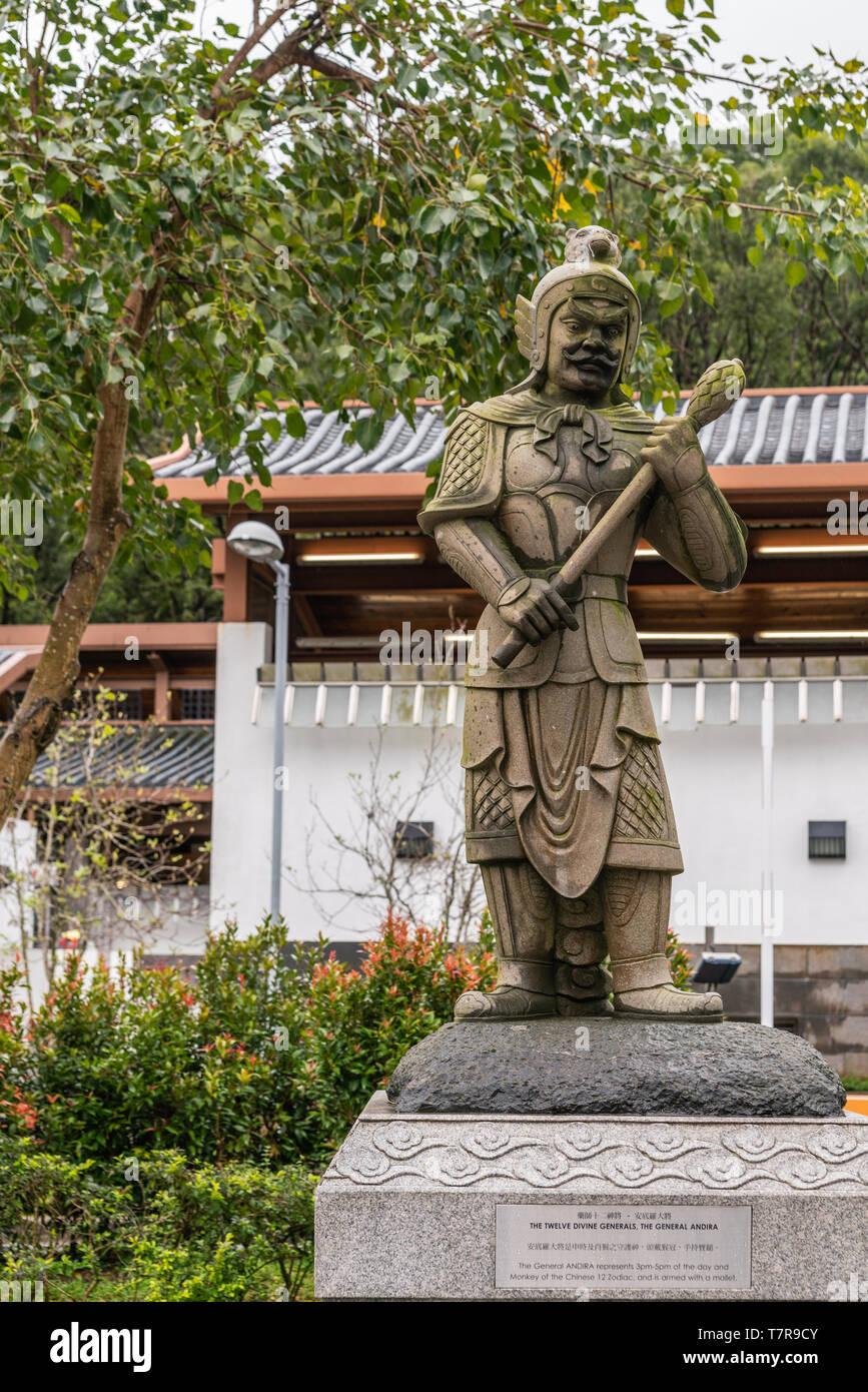 Hong Kong, China - March 7, 2019: Lantau Island. Po Lin Buddhist Monastery. Stone statue of General Andira, one of the twelve Divine Generals. Green B - Stock Image