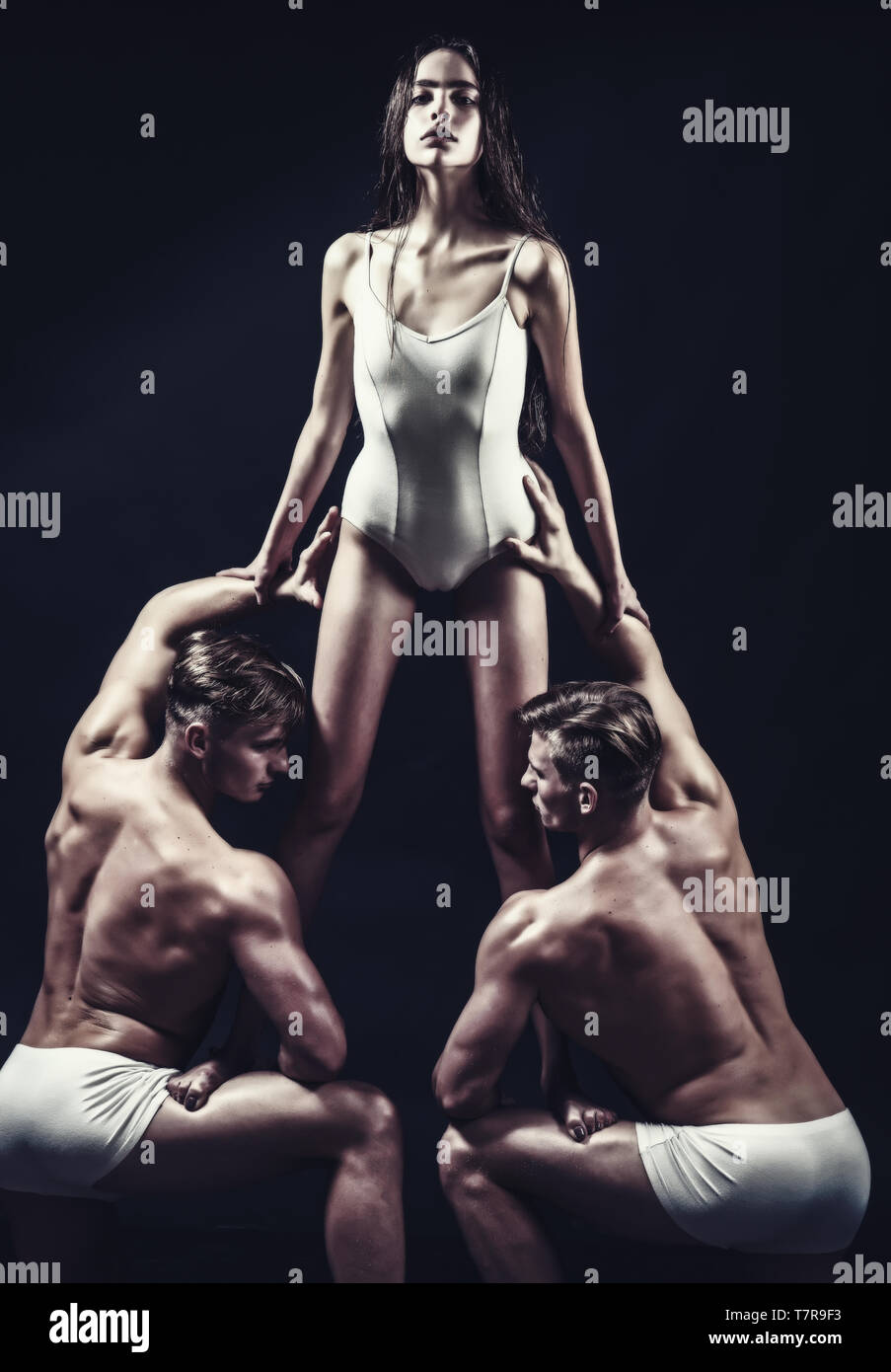Flexibility in acrobatics. flexibility of muscular men and pretty woman in white sportswear. - Stock Image