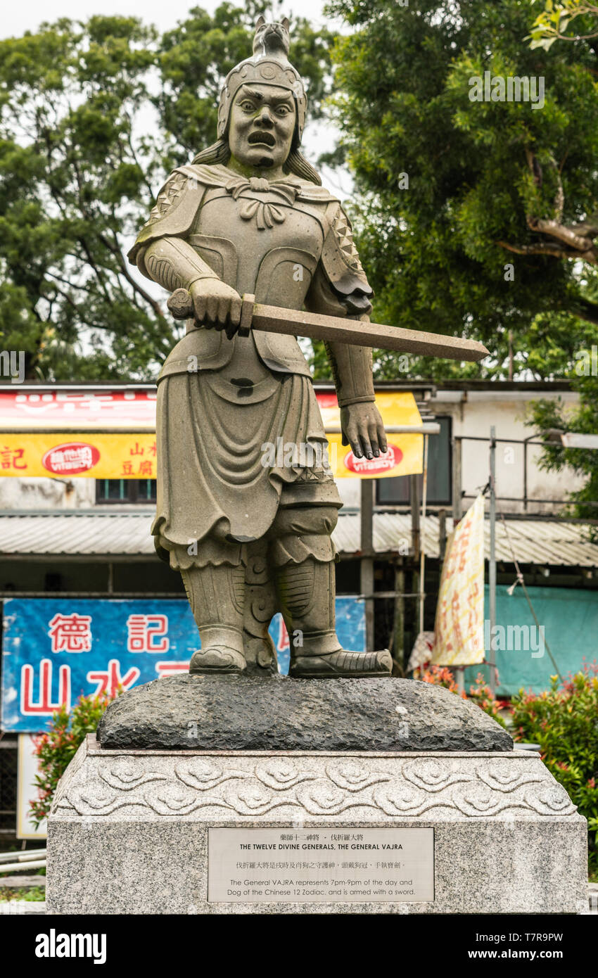 Hong Kong, China - March 7, 2019: Lantau Island. Po Lin Buddhist Monastery. Stone statue of General Vajra, one of the twelve Divine Generals. Yellow,  - Stock Image