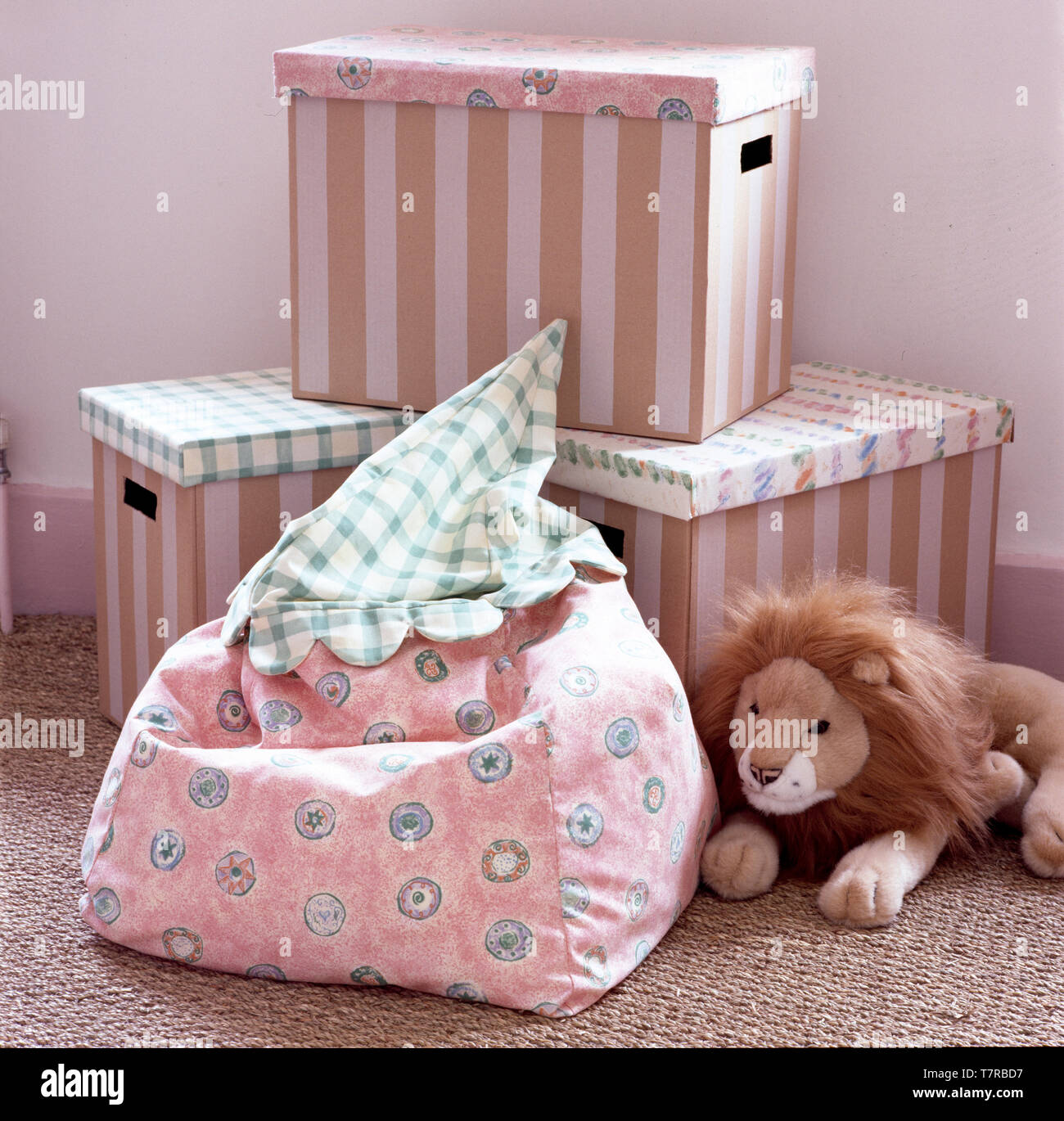 Child's bean bag and toy lion with striped storage boxes - Stock Image
