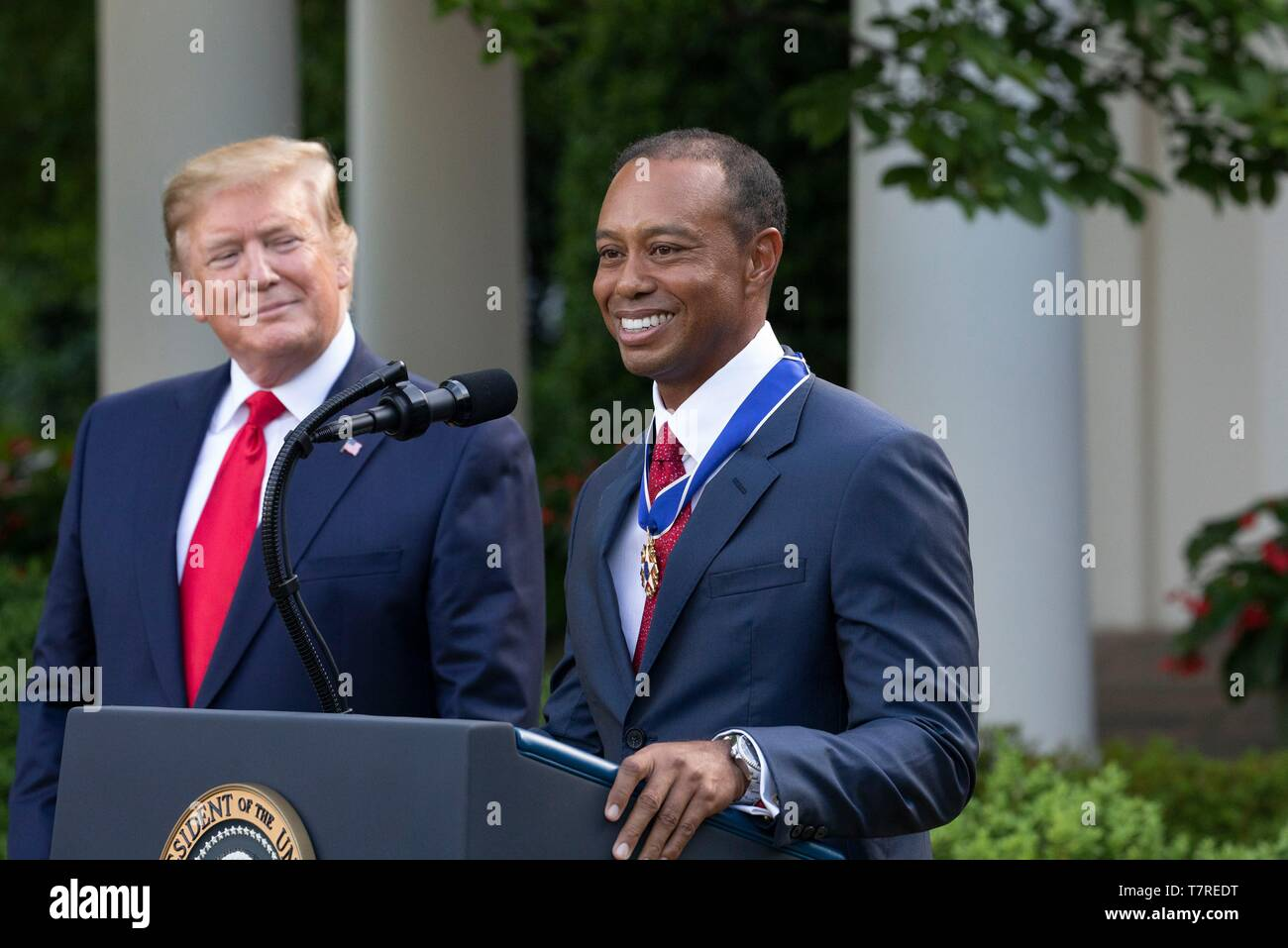 Golfer Tiger Woods delivers remarks as U.S President Donald Trump looks on after he received the Presidential Medal of Freedom during a Rose Garden ceremony at the White House May 6, 2019 in Washington, DC. - Stock Image