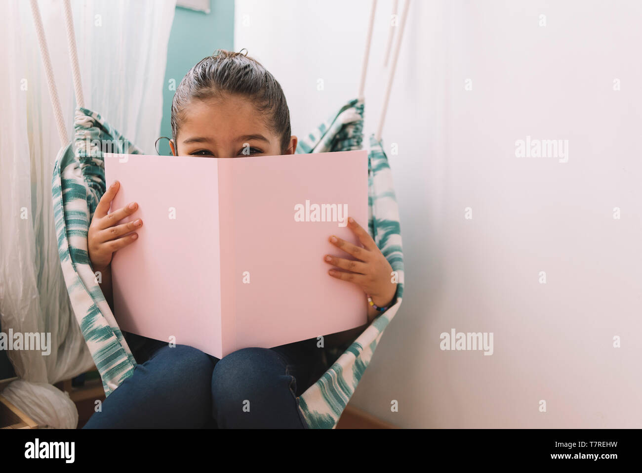 sweet happy little girl reading a book in her room near the window, funny lovely child having fun in kids room, copy space for text Stock Photo