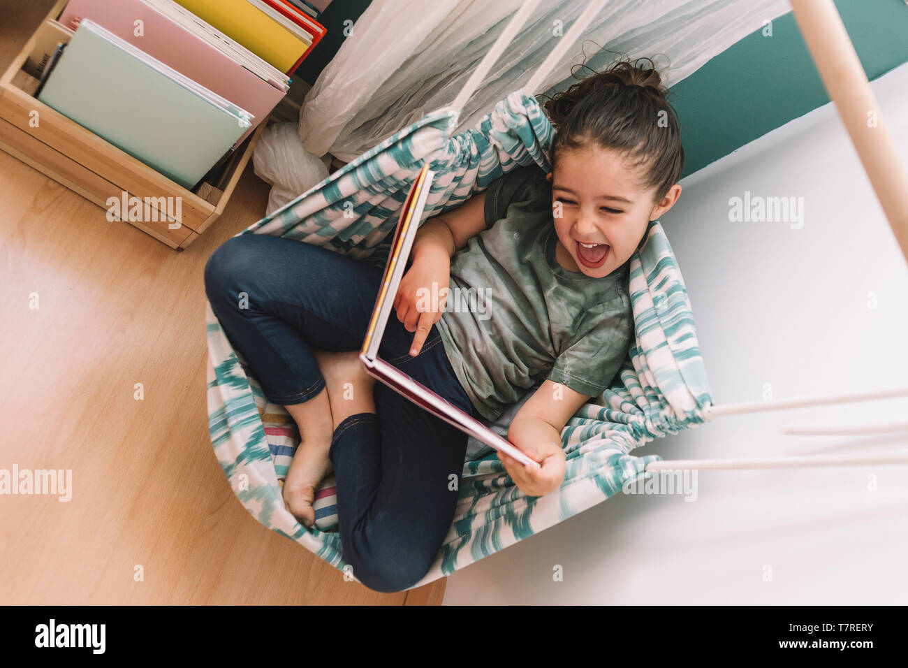 little girl laughs out loud reading a book at home near the window, funny lovely child having fun in her kids room, copy space for text Stock Photo