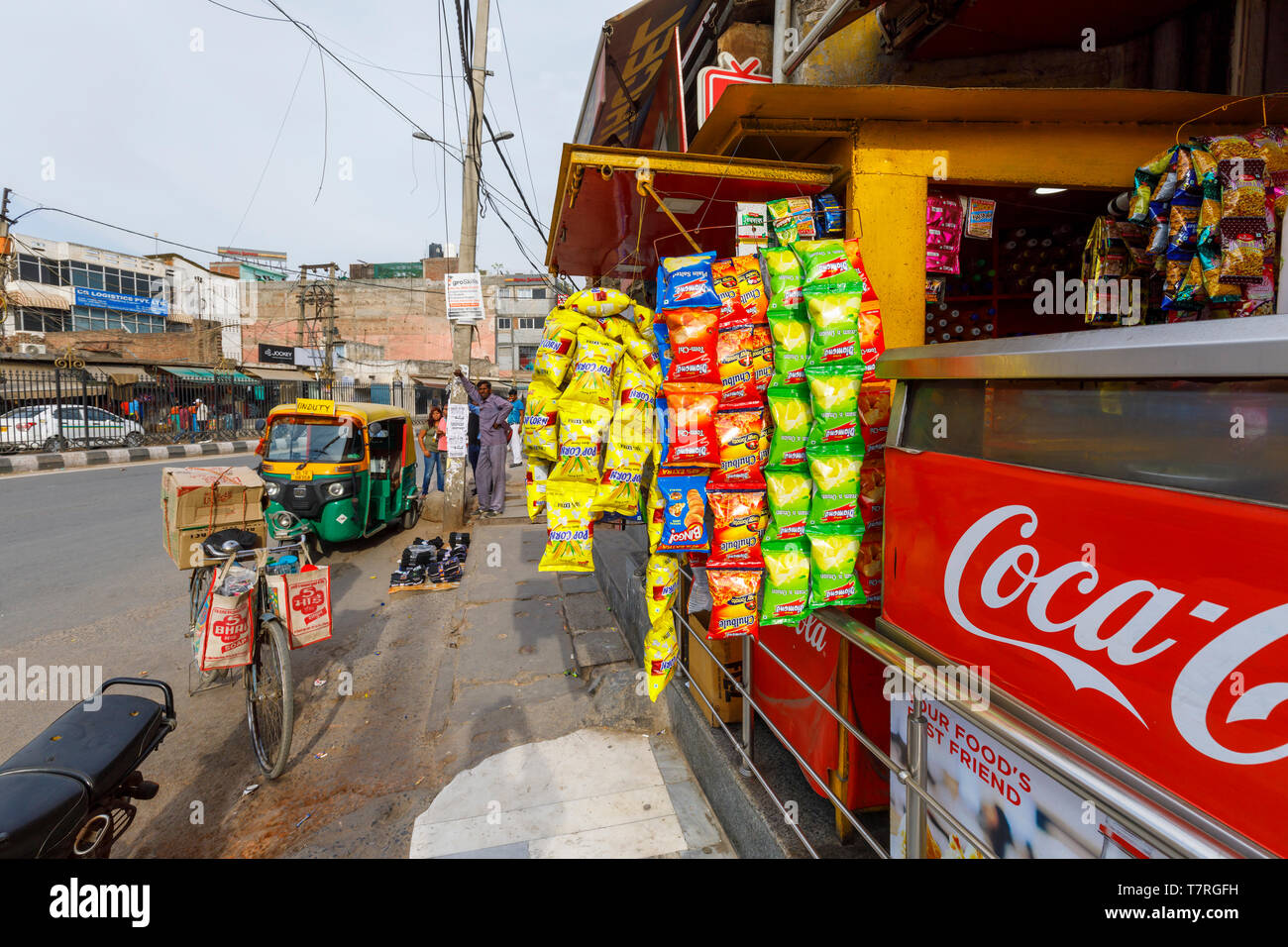 Street scene, Mahipalpur district, a suburb near Delhi Airport, New Delhi, India: local shop selling snacks with a display of colourful crisp packets - Stock Image