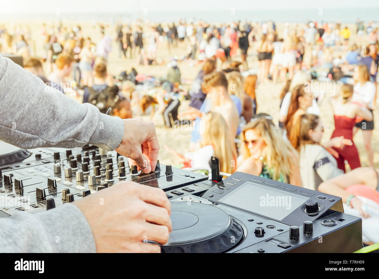 Close up of DJ's hand playing music at turntable at beach party festival - Crowd people dancing and having fun in club outdoor - Stock Image