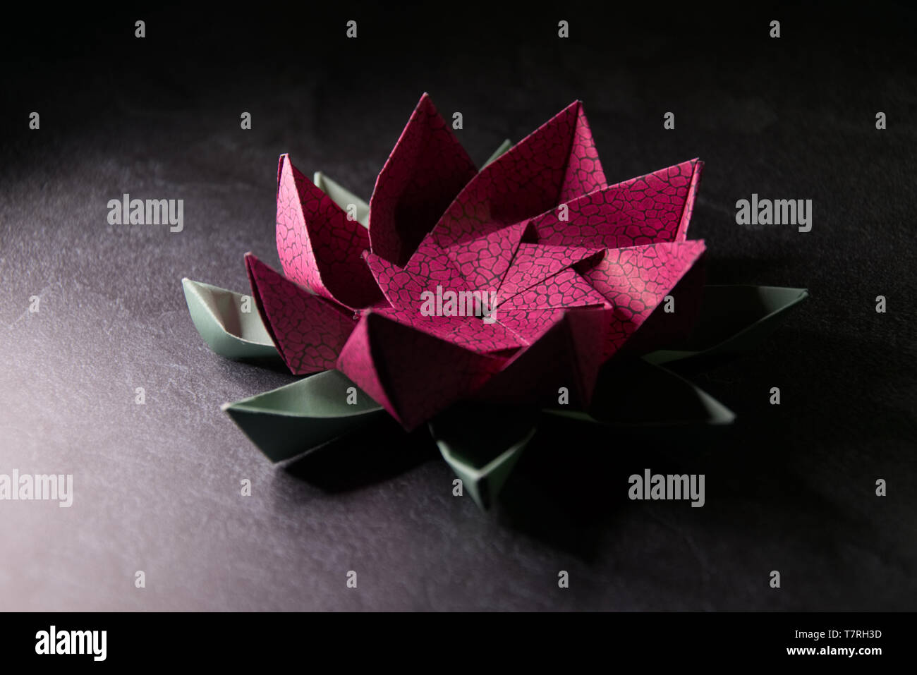Pink Origami Lotus Flower - Ars and Crafts, Paper Art on Textured Stone Backgrund - Stock Image