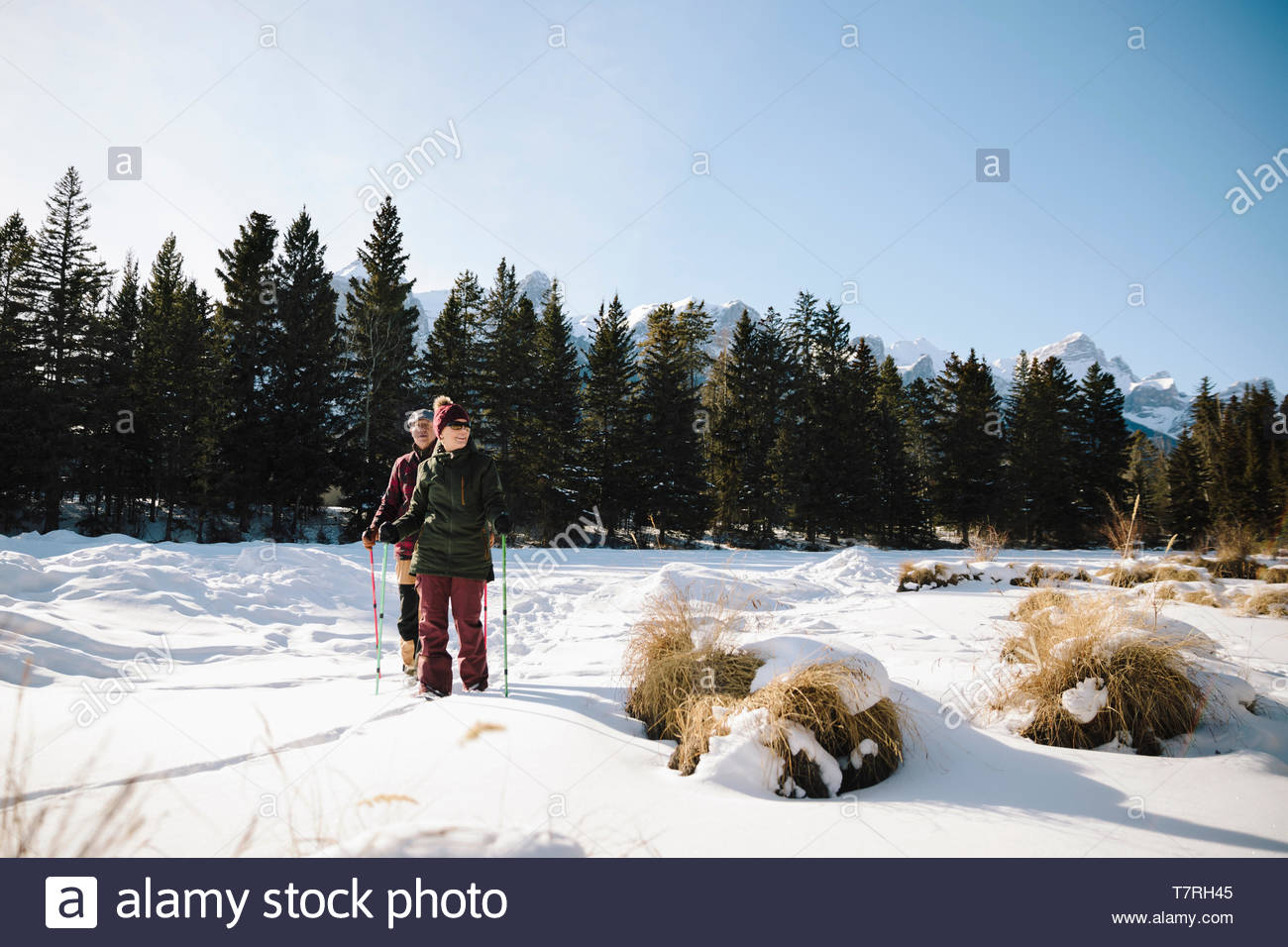 Senior couple snowshoeing in field - Stock Image