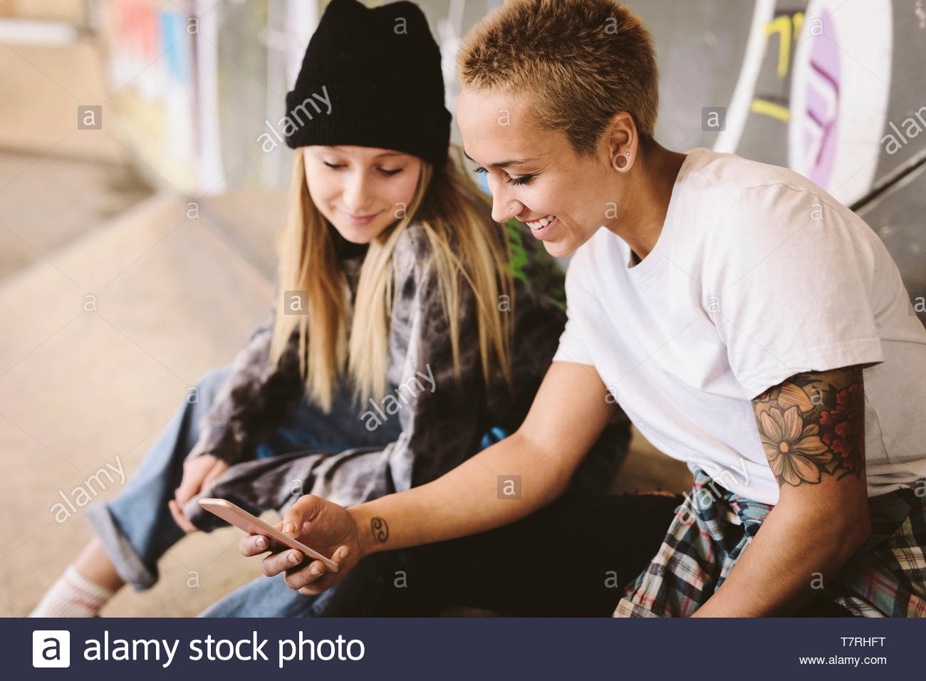 Young female skateboarders using smart phone at indoor skate park - Stock Image