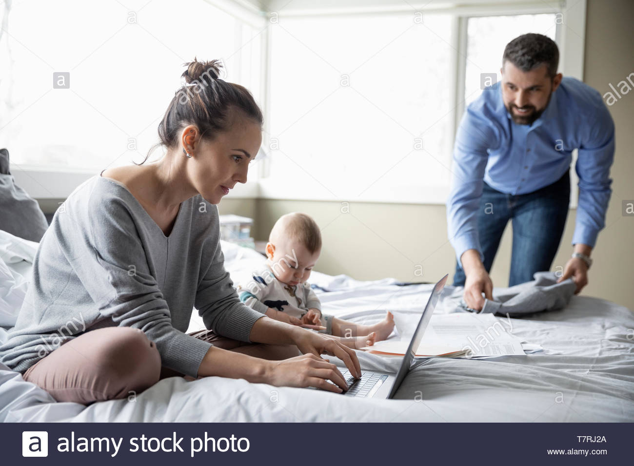 Parents with baby working from home, getting ready for work - Stock Image