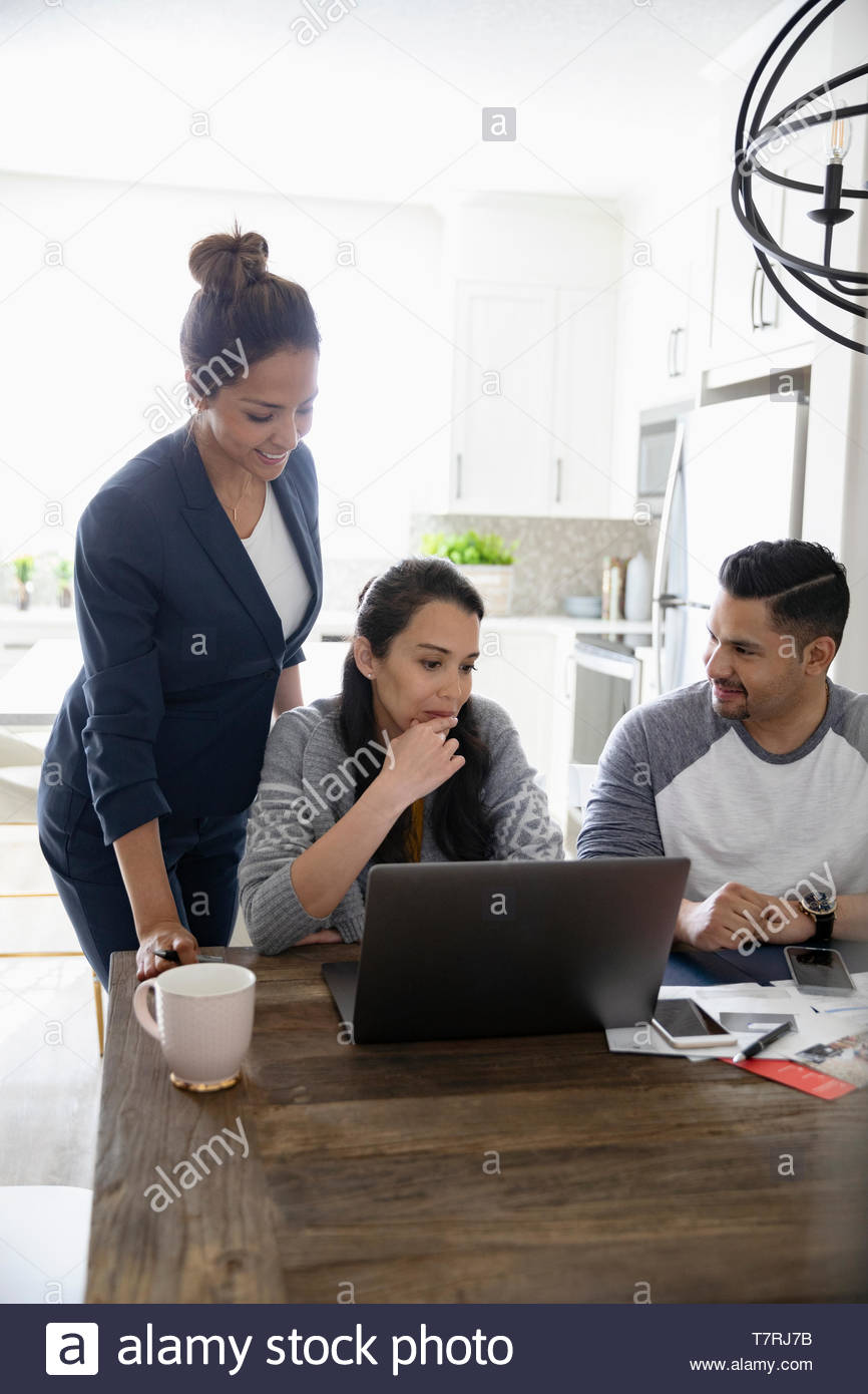 Financial advisor meeting with couple at laptop in kitchen - Stock Image
