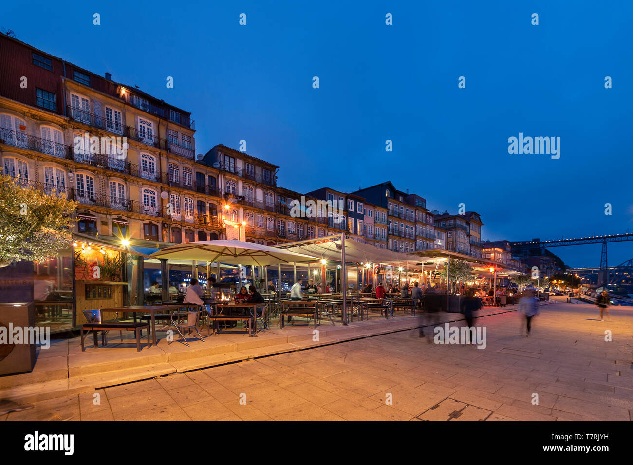 The Ribeira waterfront district of Porto, Portugal at night with illuminated restaurants and cafes. - Stock Image