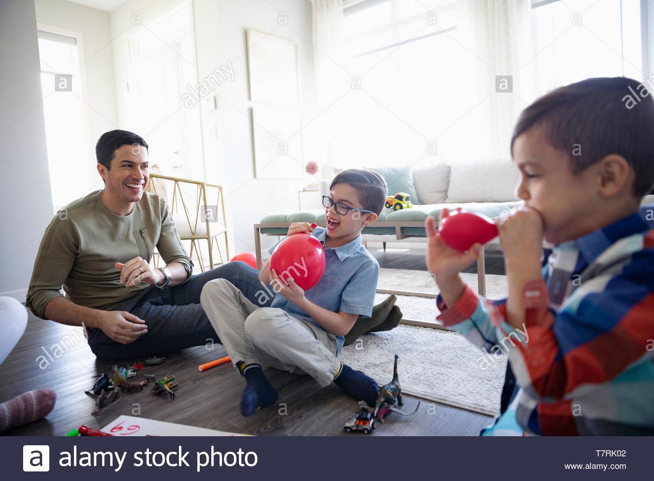 Father and sons blowing up balloons in living room - Stock Image