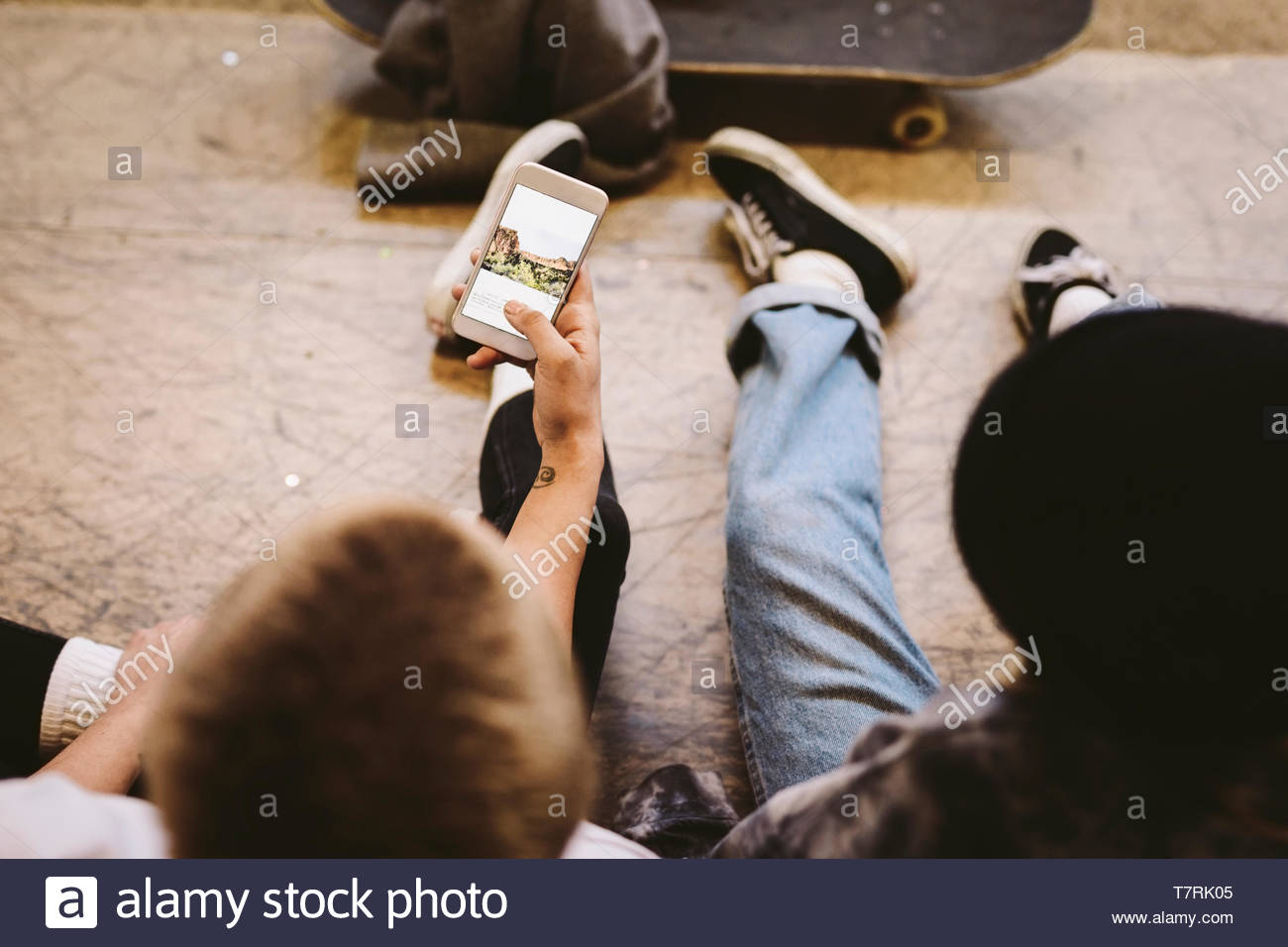Friends hanging out, using smart phone - Stock Image