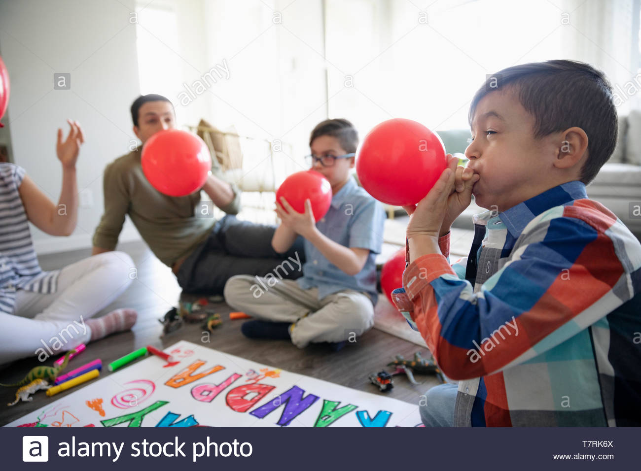 Family blowing up birthday balloons - Stock Image