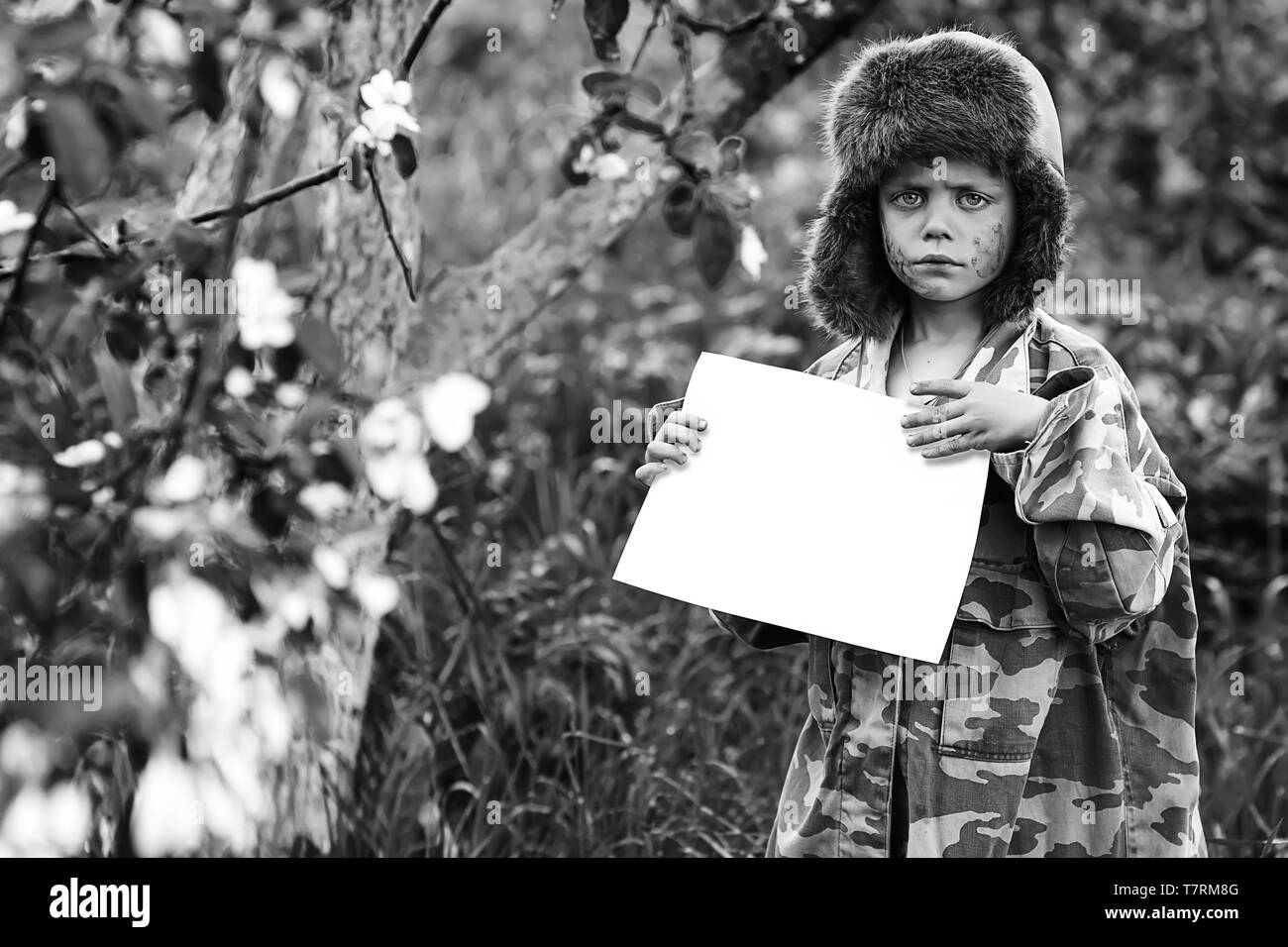 a boy in a camouflage uniform and a hat with earflaps stands in an Apple orchard with a clean white sheet - Stock Image