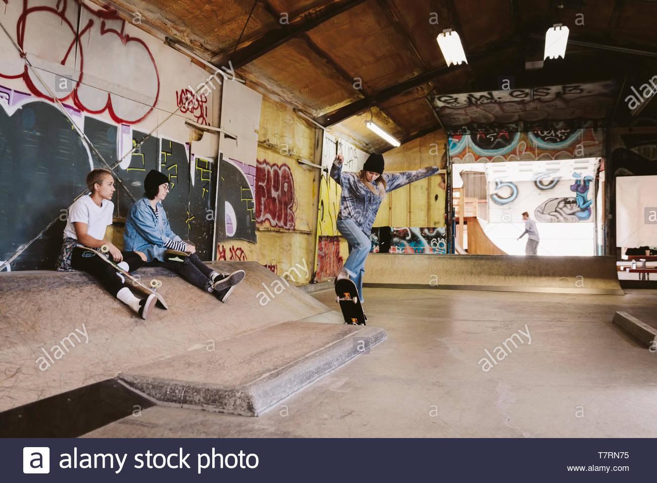 Friends skateboarding at indoor skate park - Stock Image