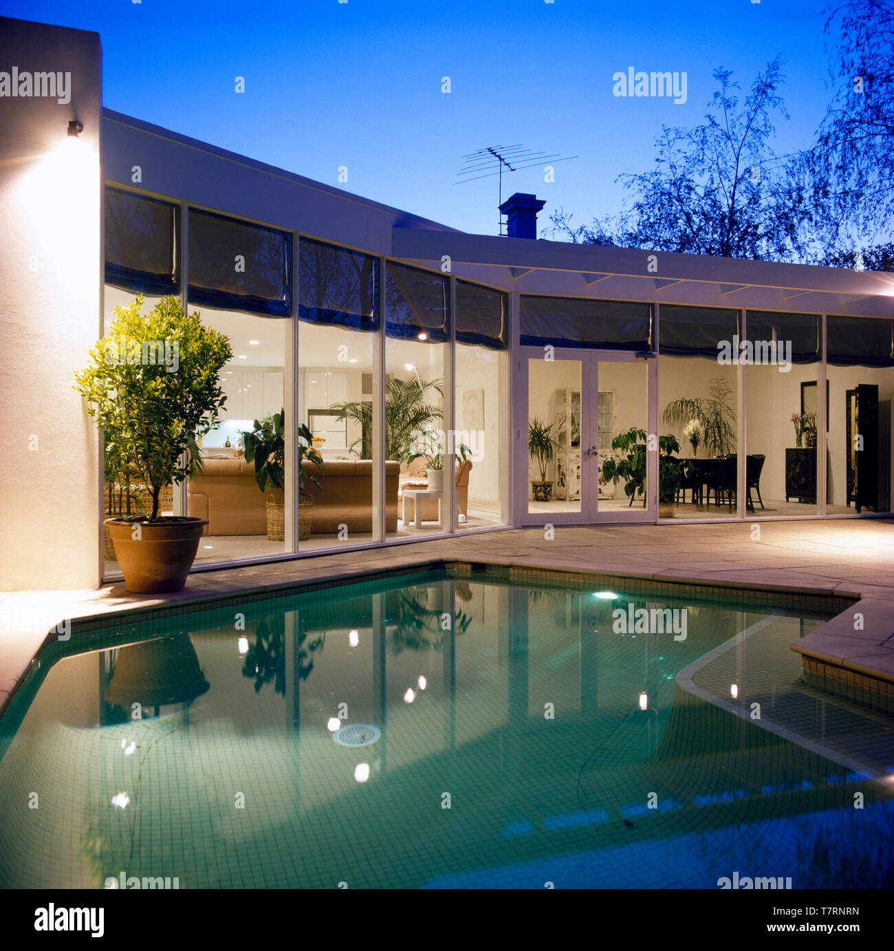 Swimming pool in front of a single storey house with glass ...