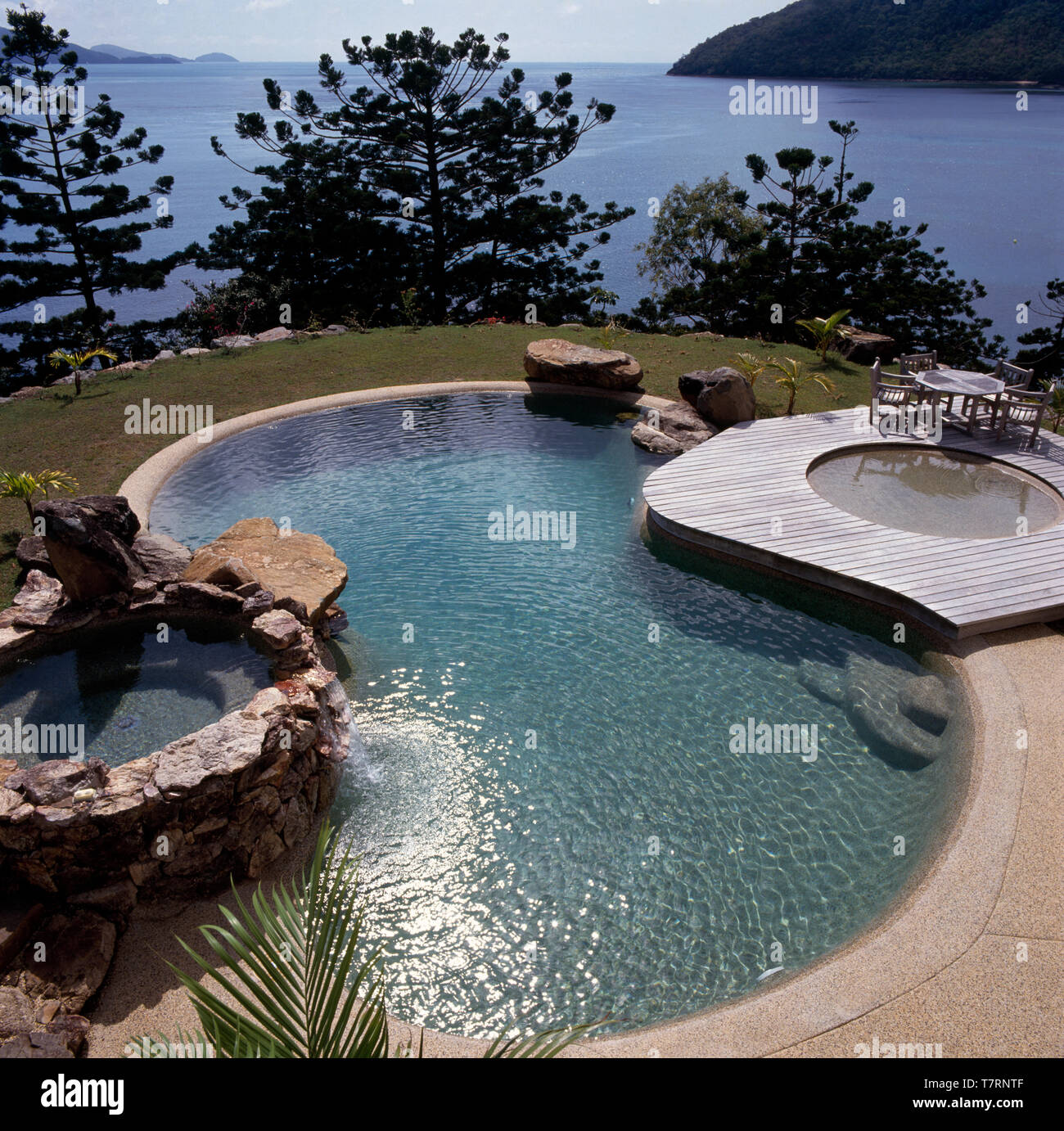 Curved swimming pool and hot tubs in a coastal garden with a ...
