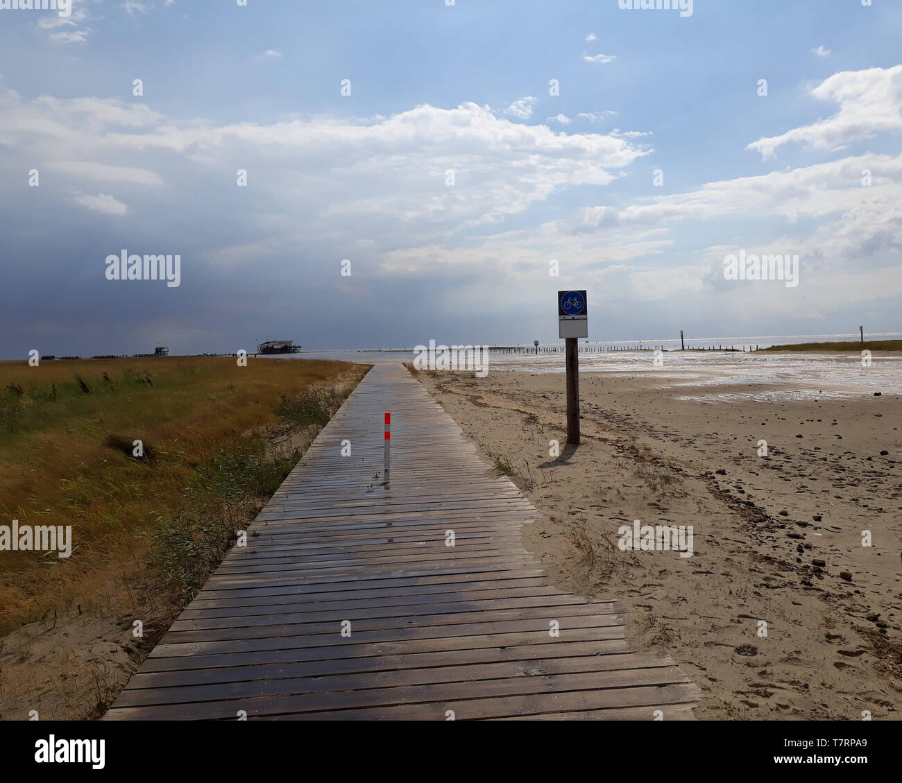 Wooden jetty at the North Sea near sankt Peter Ording with clouds and sand and sea - Stock Image