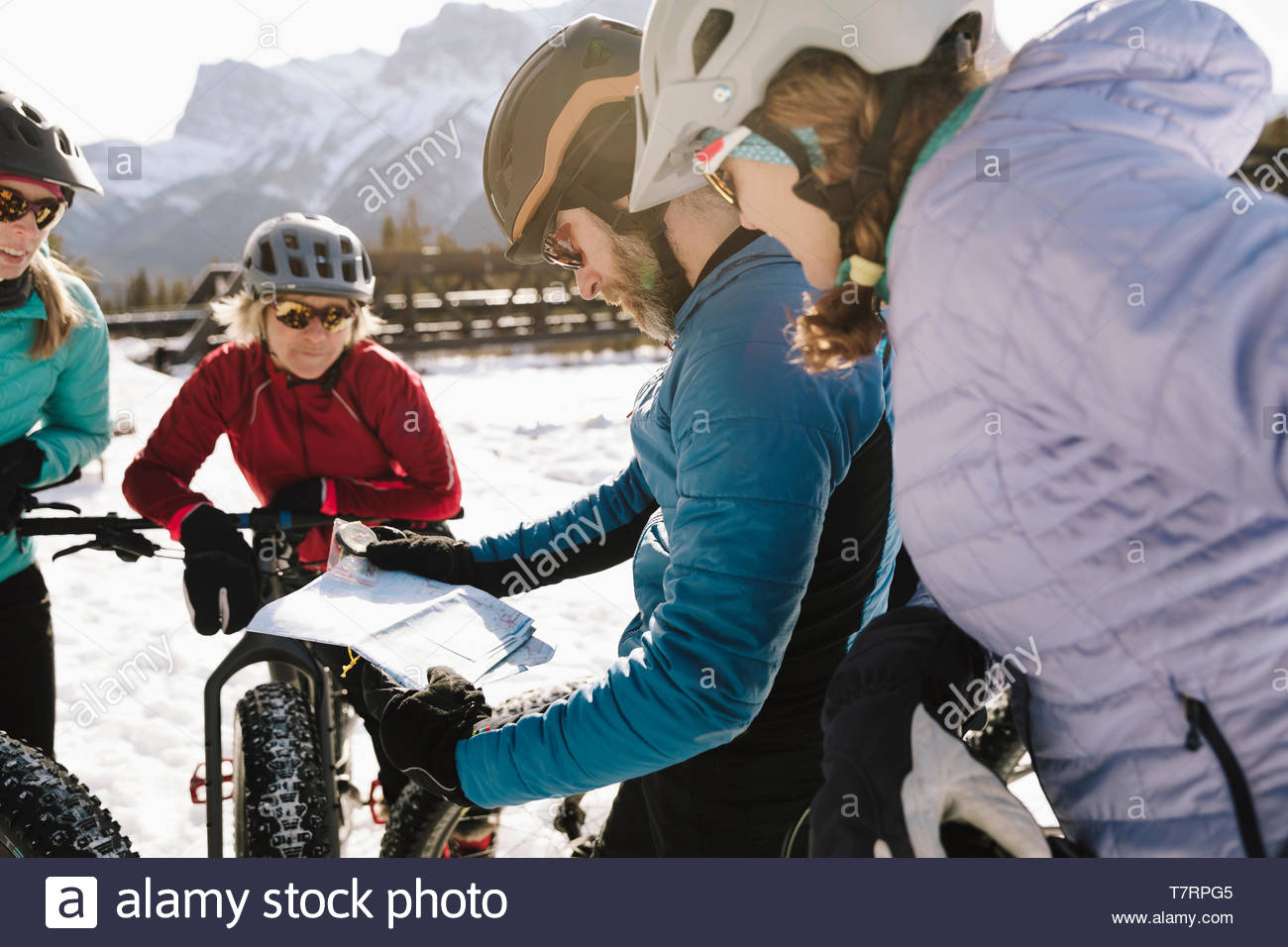 Friends with map fat biking in snow - Stock Image