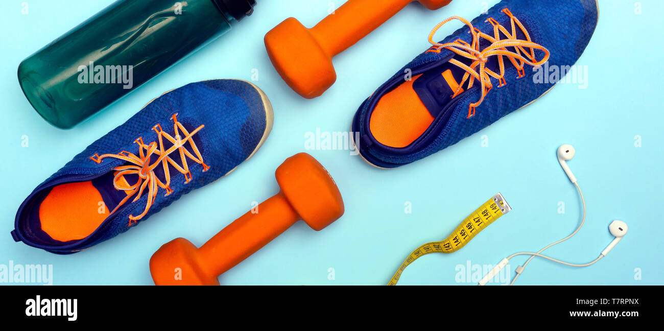 Sport concept with sport equipment composition. Sneakers, dumbbells, bottle of water on bright blue background. Weight loss, flat lay Stock Photo