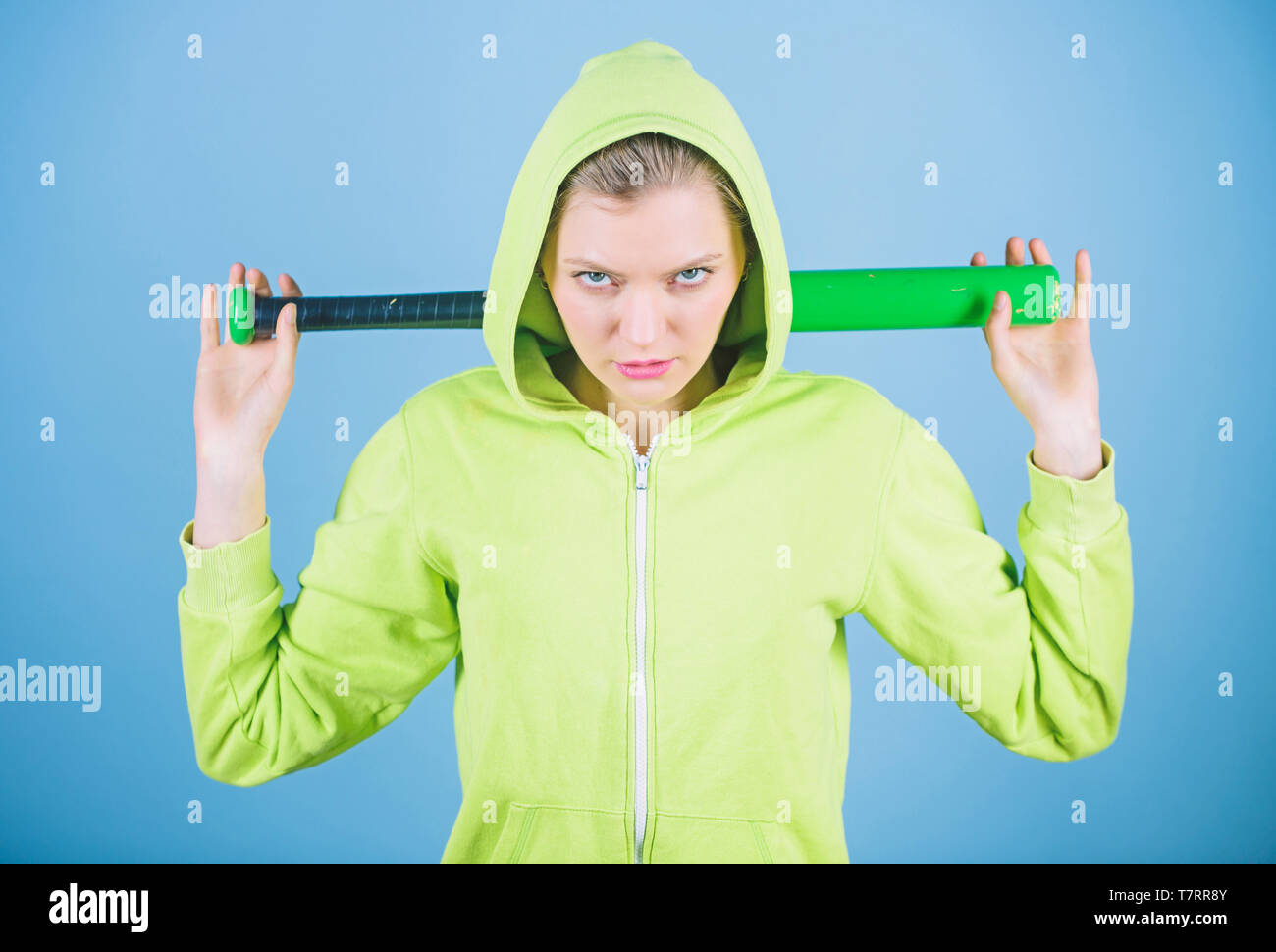 Baseball female player concept. She is dangerous. Sport game. Woman play baseball game or going to beat someone. Girl hooded jacket hold baseball bat blue background. Woman in baseball sport. - Stock Image
