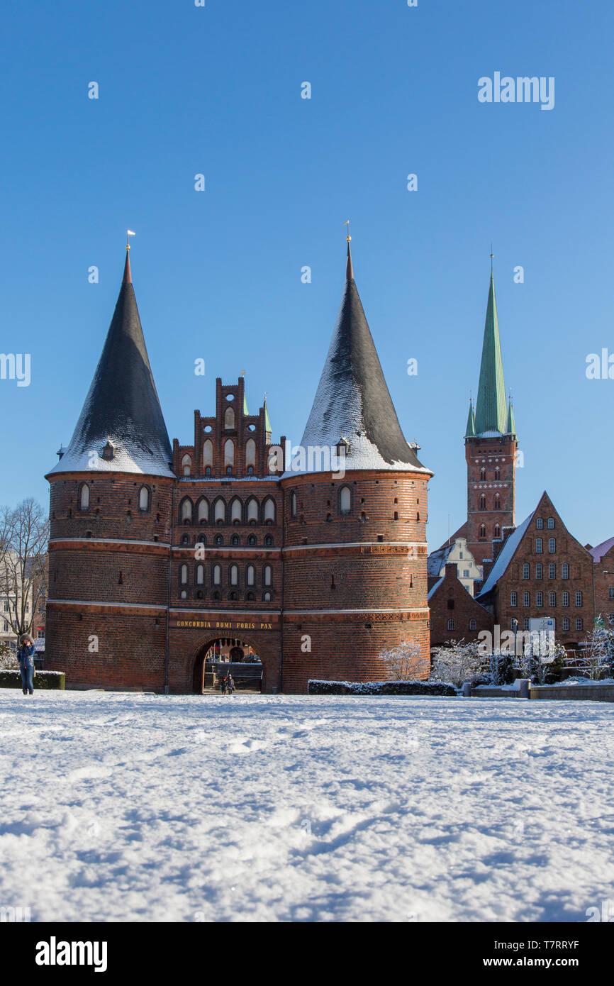 The Brick Gothic city gate Holstentor/ Holstein Gate in the Hanseatic town Lübeck in winter, Schleswig-Holstein, Germany - Stock Image