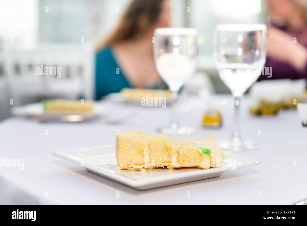Table with glasses of water in restaurant or wedding reception white table tablecloth plates with yellow cake slices and background of guests eating - Stock Image