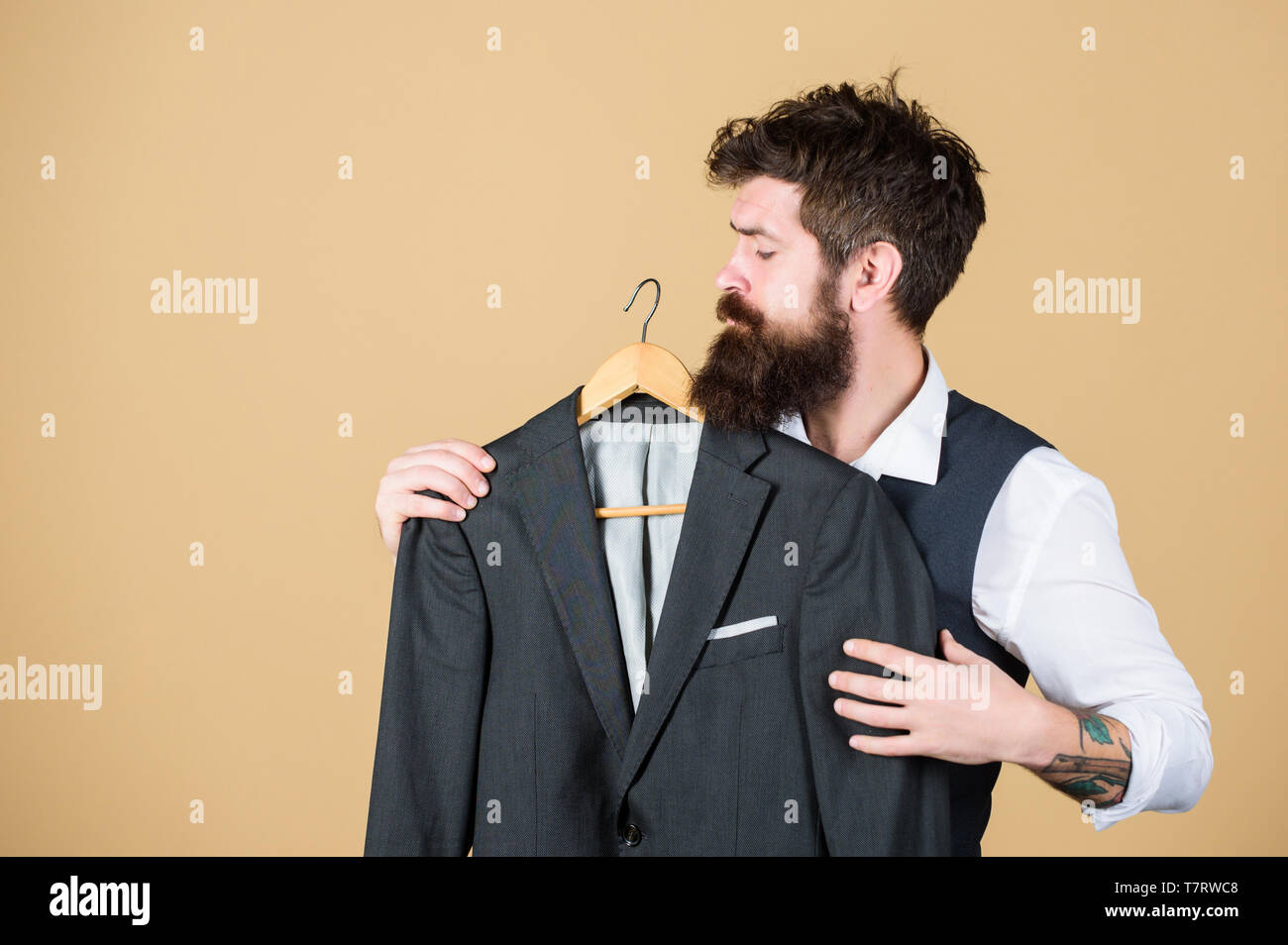 When the invite says formal. Bearded man at formal wear boutique. Hipster choosing formal suit jacket in wardrobe. Classy formal look of fashion model. - Stock Image