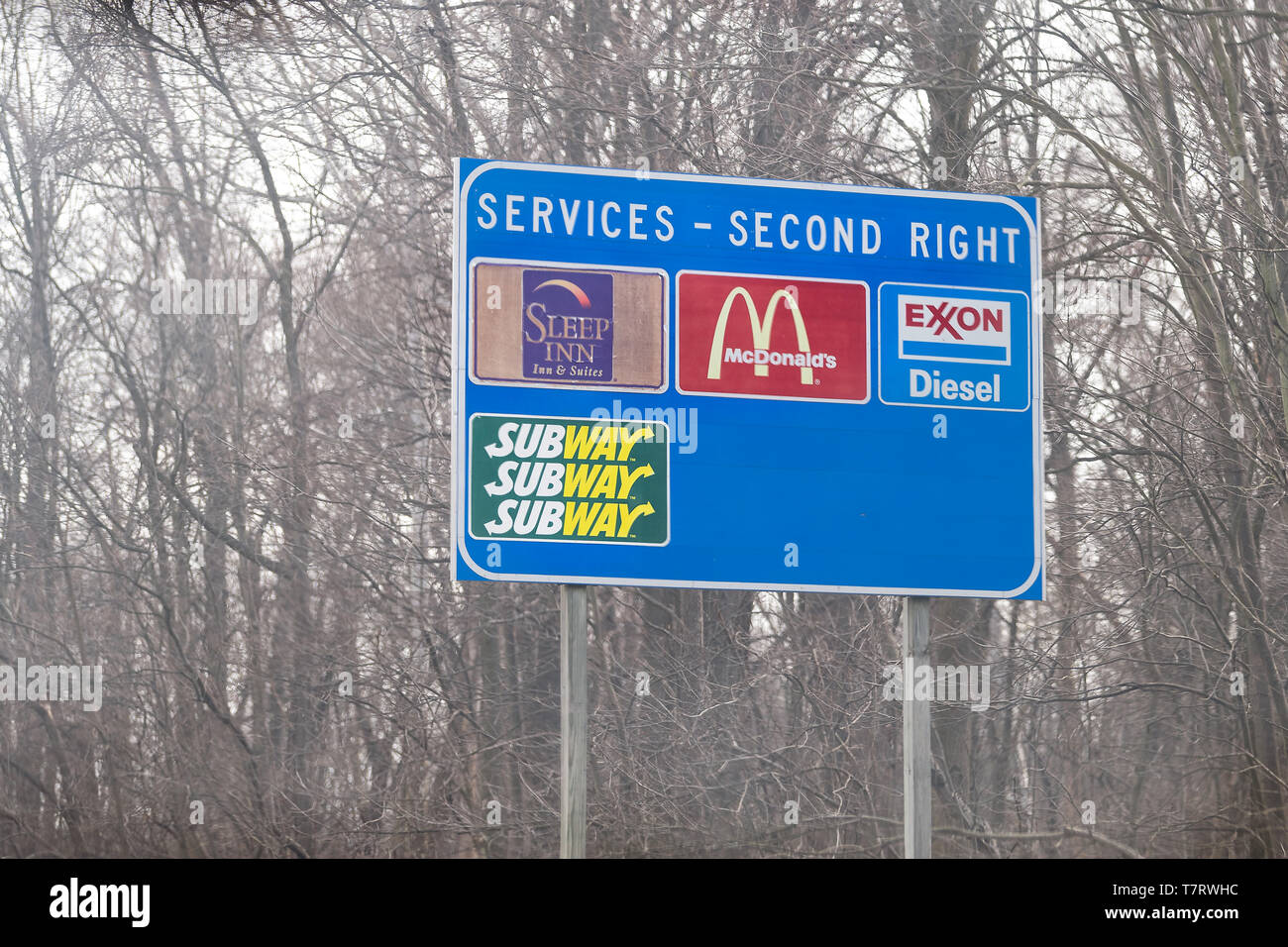 Leesburg, USA - April 6, 2018: Rural Virginia countryside in spring with blue exit sign on highway for food and service such as mcdonalds fast food, s - Stock Image