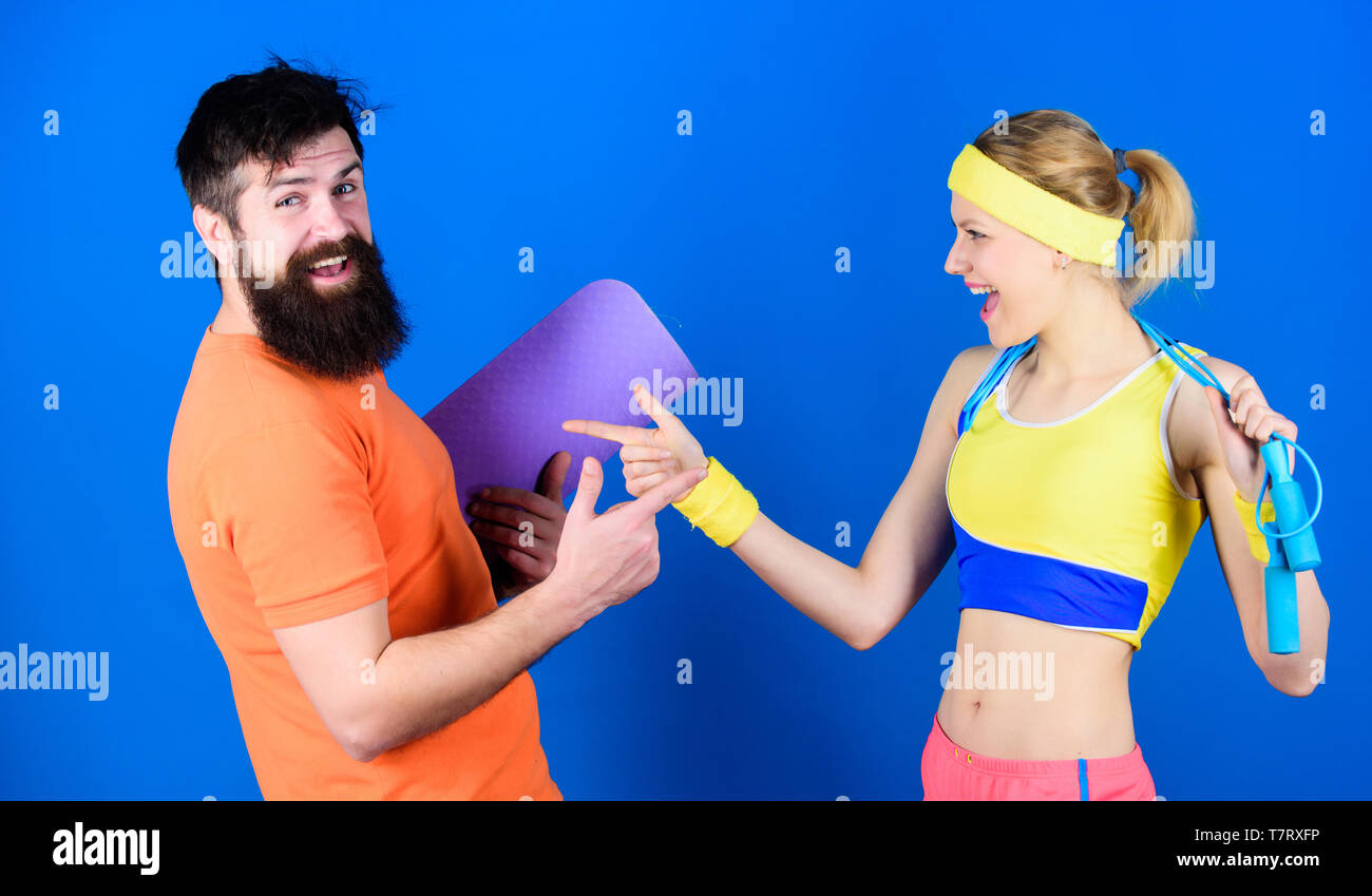 Together Everyone Achieves More. Athletic Success. Sport equipment. Strong muscles and body. Happy woman and bearded man workout in gym. Sporty couple training with fitness mat and skipping rope. - Stock Image