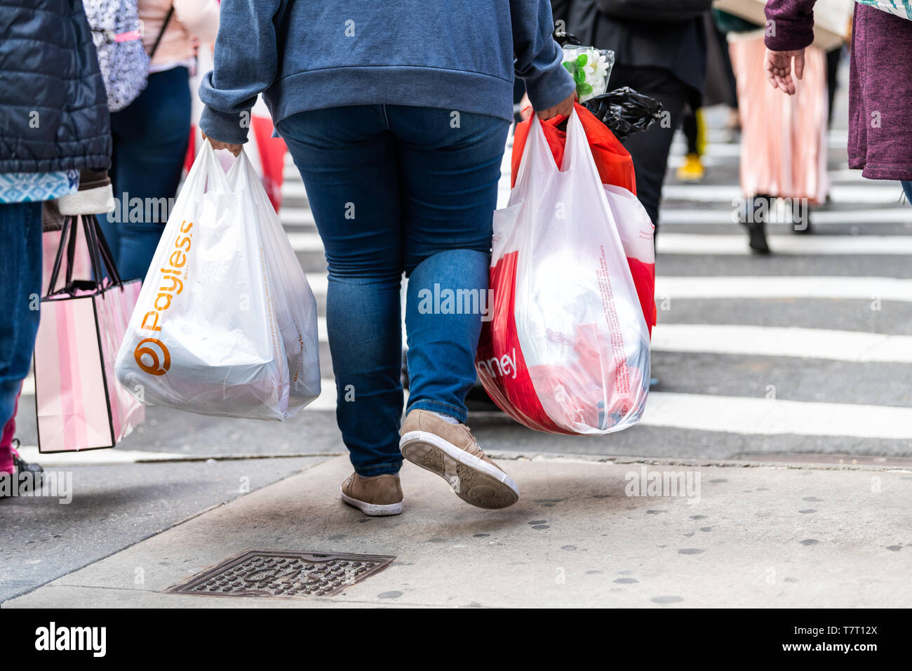 New York City, USA - April 6, 2018: Manhattan NYC sidewalk in midtown on 6th avenue road and closeup of people walking woman carrying Payless and JCPe Stock Photo