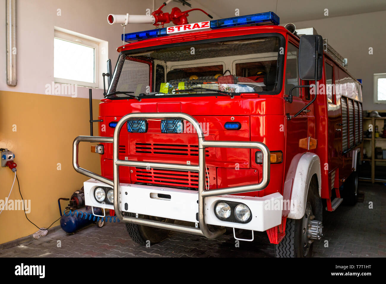 The front of the truck of an old Polish fire truck with visible blue light signals, water cannon and the Polish word 'STRAZ' translated into English ' - Stock Image
