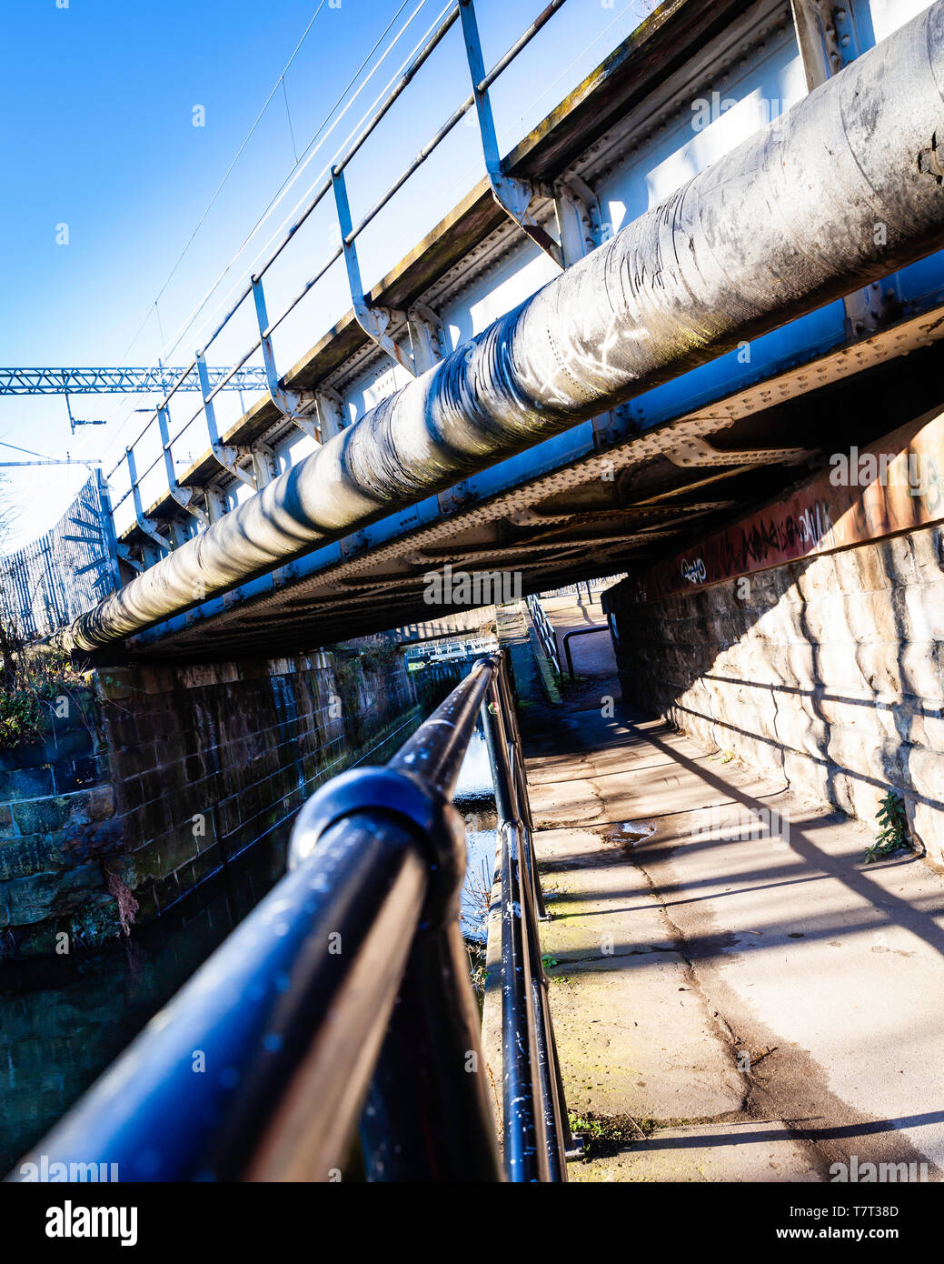 Canal towpath under a large pipe, and railway bridge. - Stock Image