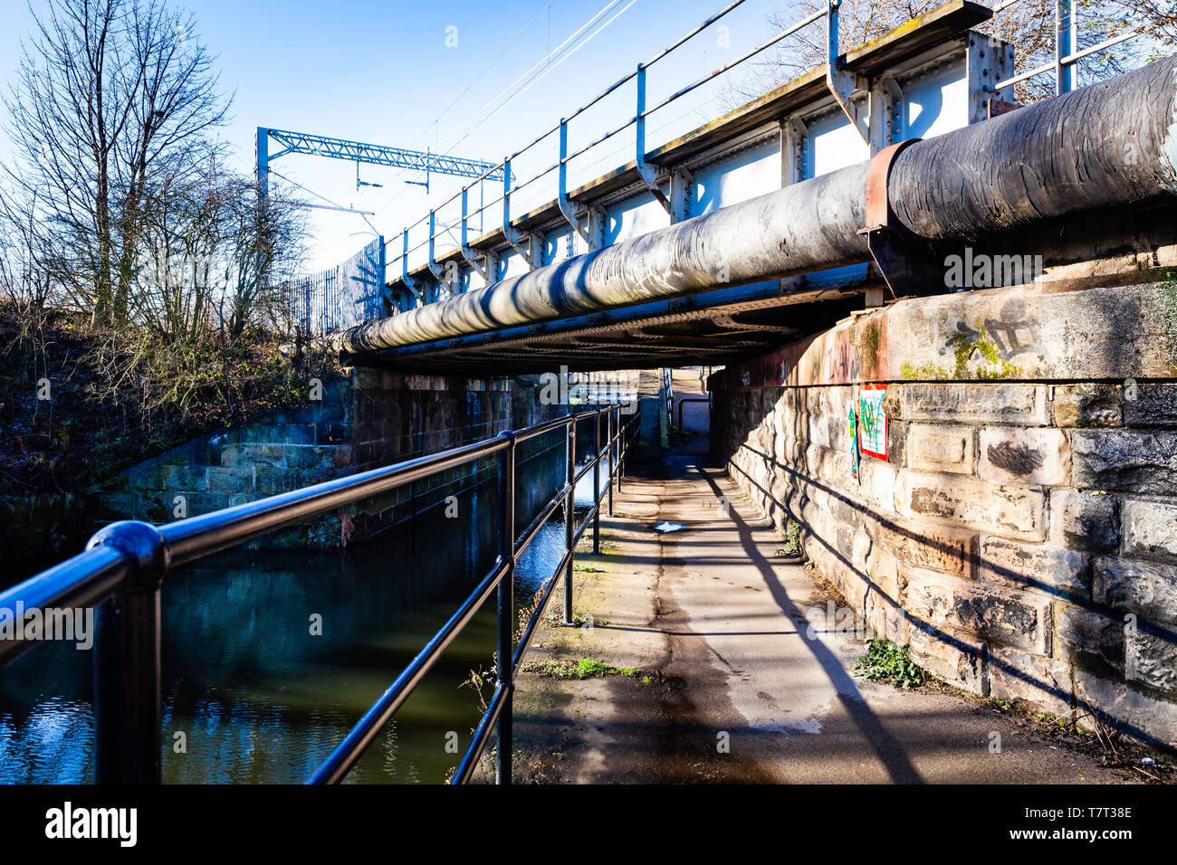 Towpath under a large pipe, and railway bridge. - Stock Image
