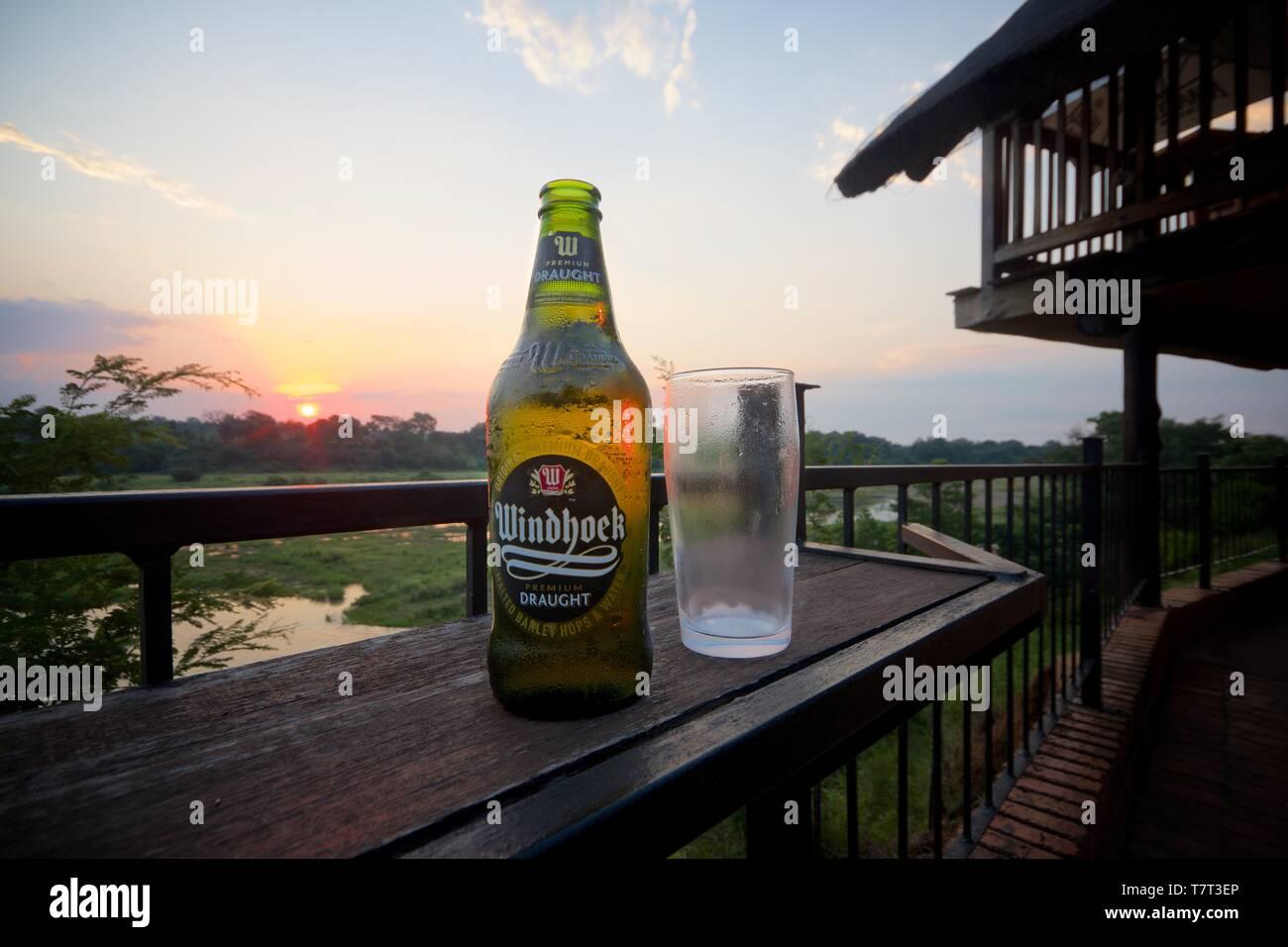 A bottle of cold Windhoek Draught beer, overlooking Crocodile river, Kruger Park. - Stock Image