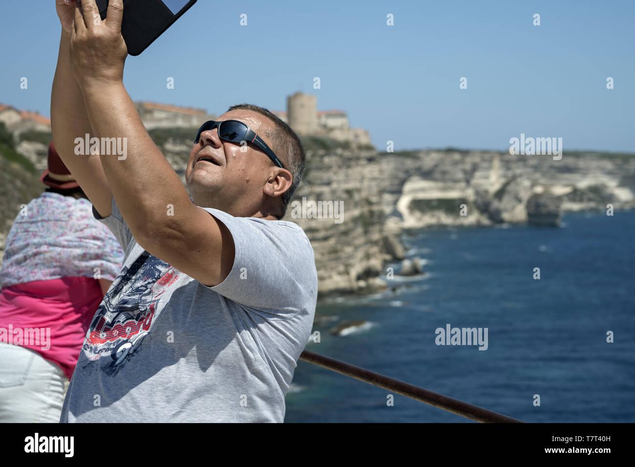 Man on holidays making selfie on the background of the cliff coast. Mann im Urlaub, der selfie auf dem Hintergrund einer Klippenküste macht. Mężczyzna - Stock Image