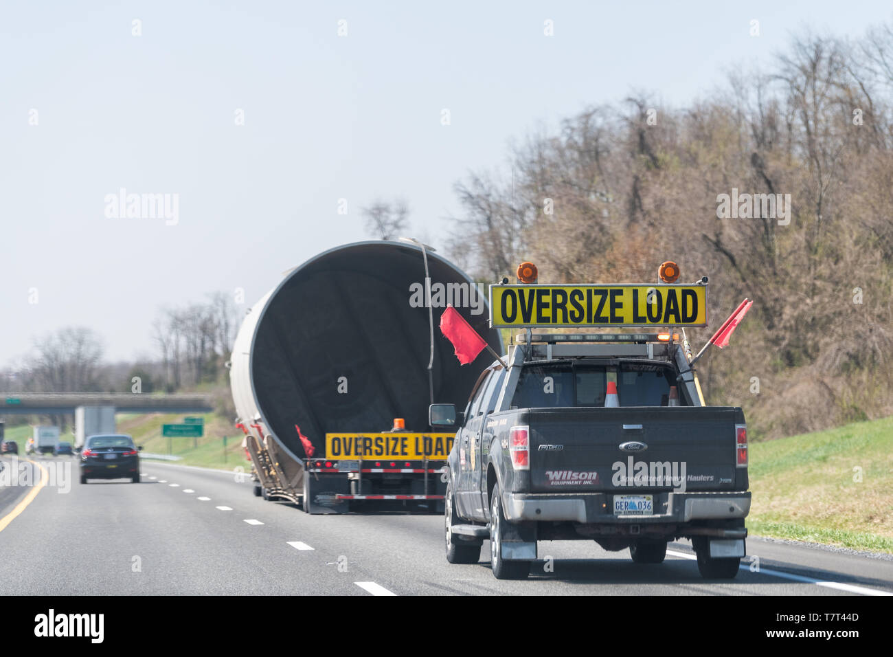 Woodstock, USA - April 18, 2018: Hauler truck trailer vehicle hauling oversize load of concrete pipe tube on interstate highway road in Virginia with  - Stock Image