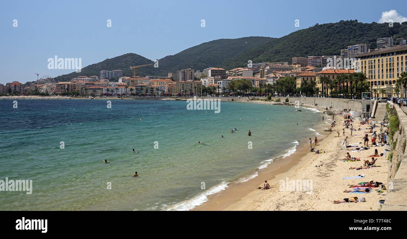Bathers and sunbathing people on the beach in Ajaccio. Badende und Sonnenanbeter am Strand von Ajaccio. Kąpiący się i opalający się ludzie na plaży. - Stock Image