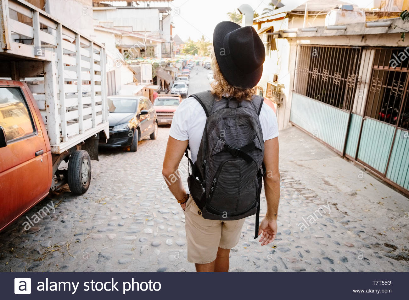 Young male tourist with backpack walking on cobblestone street, Mexico - Stock Image