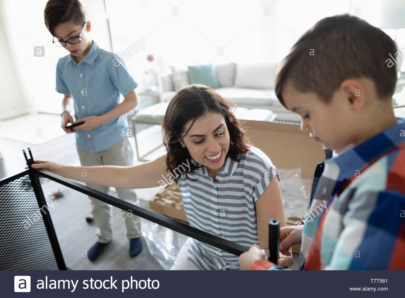 Mother and sons assembling flat pack furniture - Stock Image
