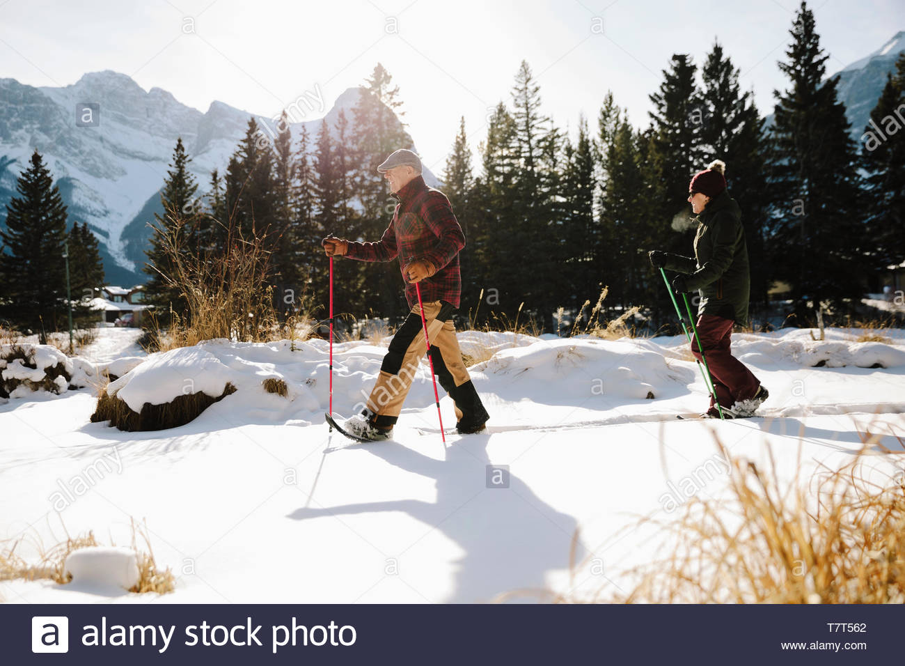 Senior couple snowshoeing below mountains - Stock Image