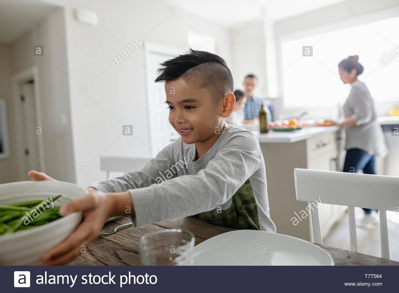Smiling boy setting the table for dinner - Stock Image