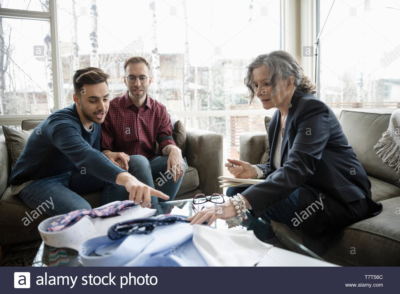 Male gay couple meeting with female wedding planner - Stock Image