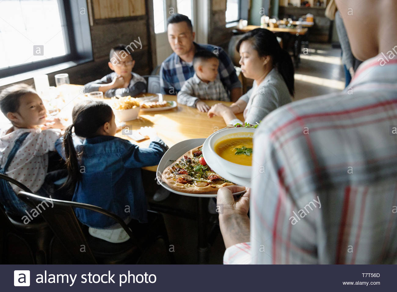 Waitress serving food to family dining in restaurant - Stock Image