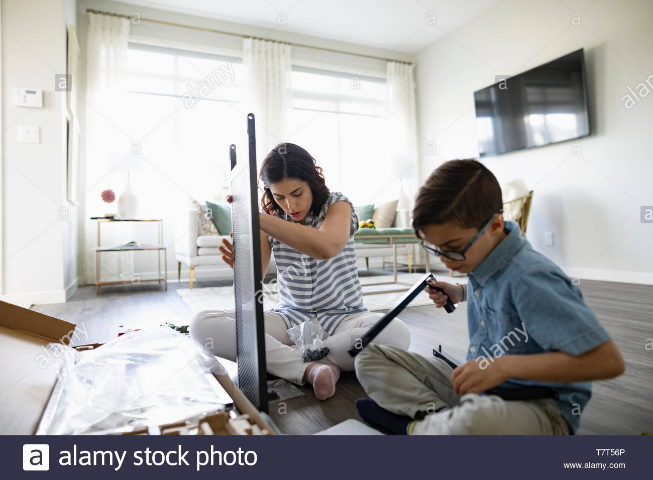 Mother and son assembling flat pack furniture - Stock Image