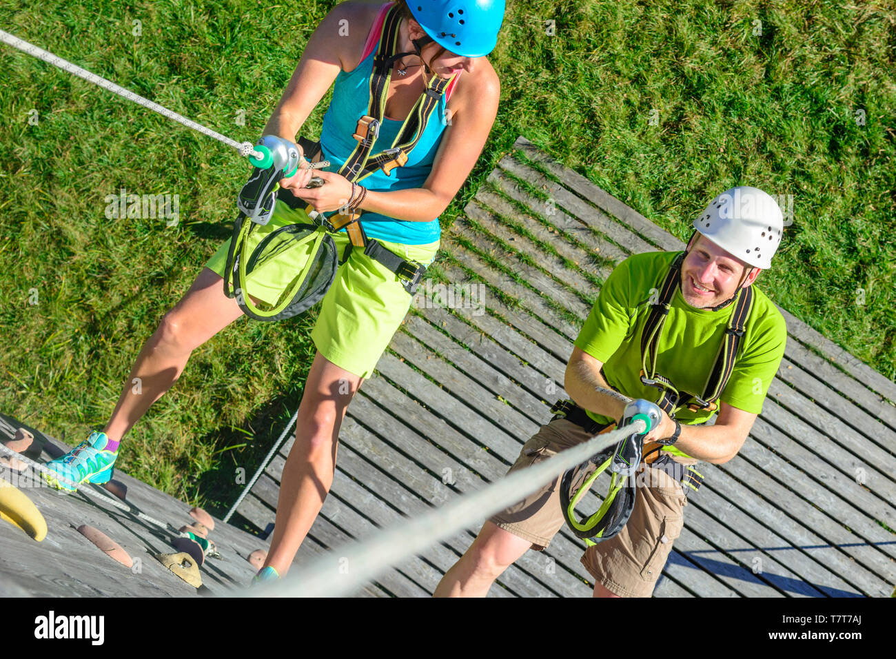 Two adults during an abseiling exercise in high ropes park Stock Photo