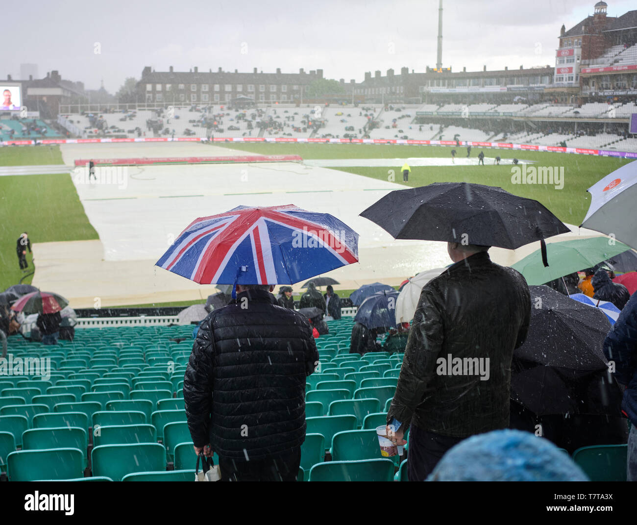 London, UK. 8th May 2019.  UK Weather: Ticket holders wait  under umbrellas as heavy rain and hail  stops play during the first One Day International between England and Pakistan at The Kia Oval.  Credit: Thomas Bowles/Alamy Live News Stock Photo
