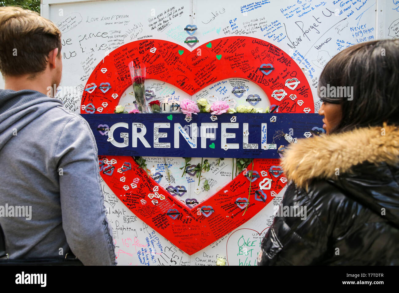 June 14, 2018 - London, United Kingdom - People seen looking at a Grenfell placard..On 14 June 2017, a fire broke out in the 24-storey Grenfell Tower block of flats in North Kensington, West London where 72 people died, more than 70 others were injured and 223 people escaped..The UK Government is to fund an estimated £200 million to replacement of unsafe Grenfell style cladding on around 170 high-rise private residential buildings after private building owners failed to take action. Communities Secretary James Brokenshire said inaction from building owners had compelled the government to act. Stock Photo