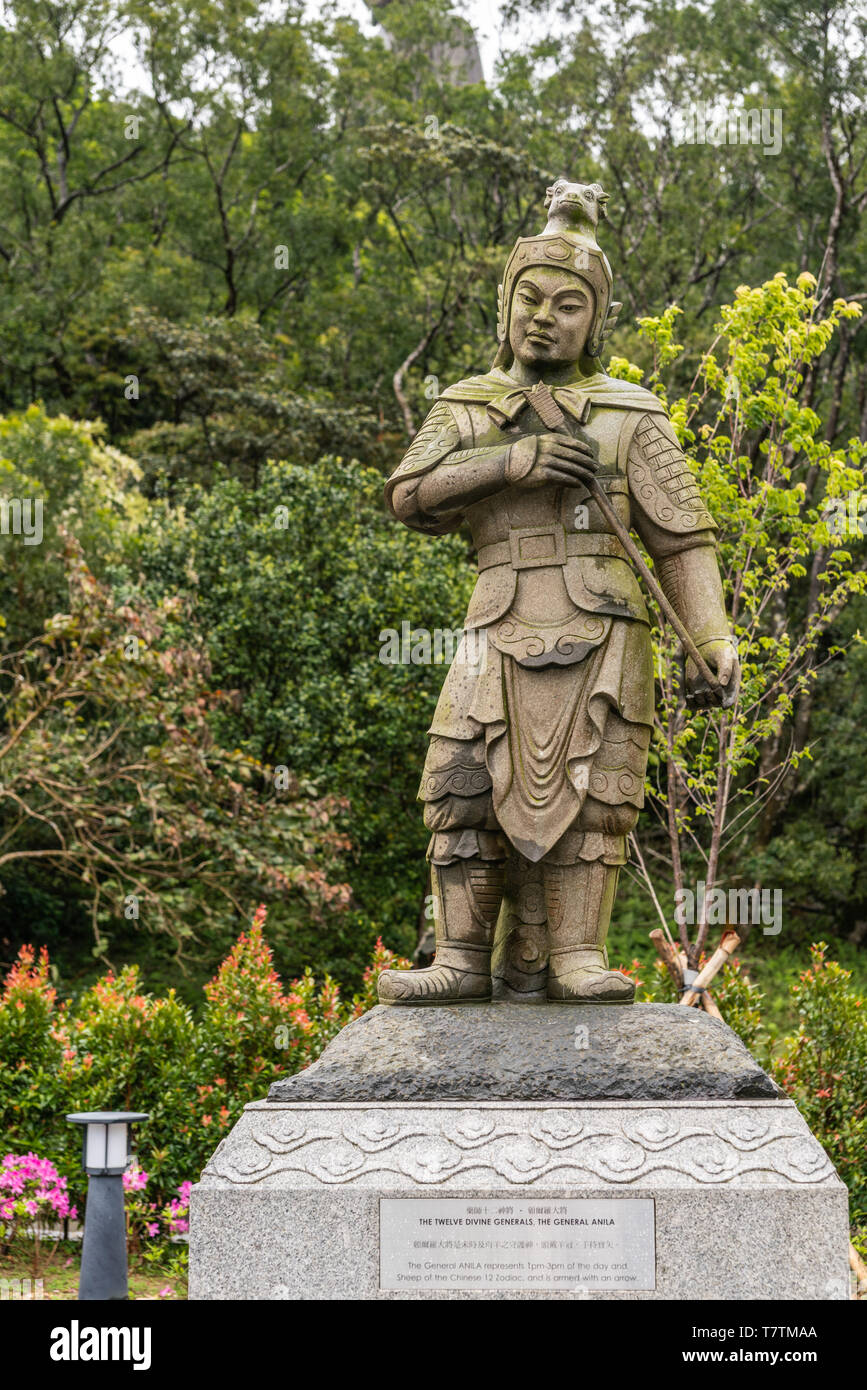Hong Kong, China - March 7, 2019: Lantau Island. Po Lin Buddhist Monastery. Stone statue of General Anila, one of the twelve Divine Generals. Green fo - Stock Image